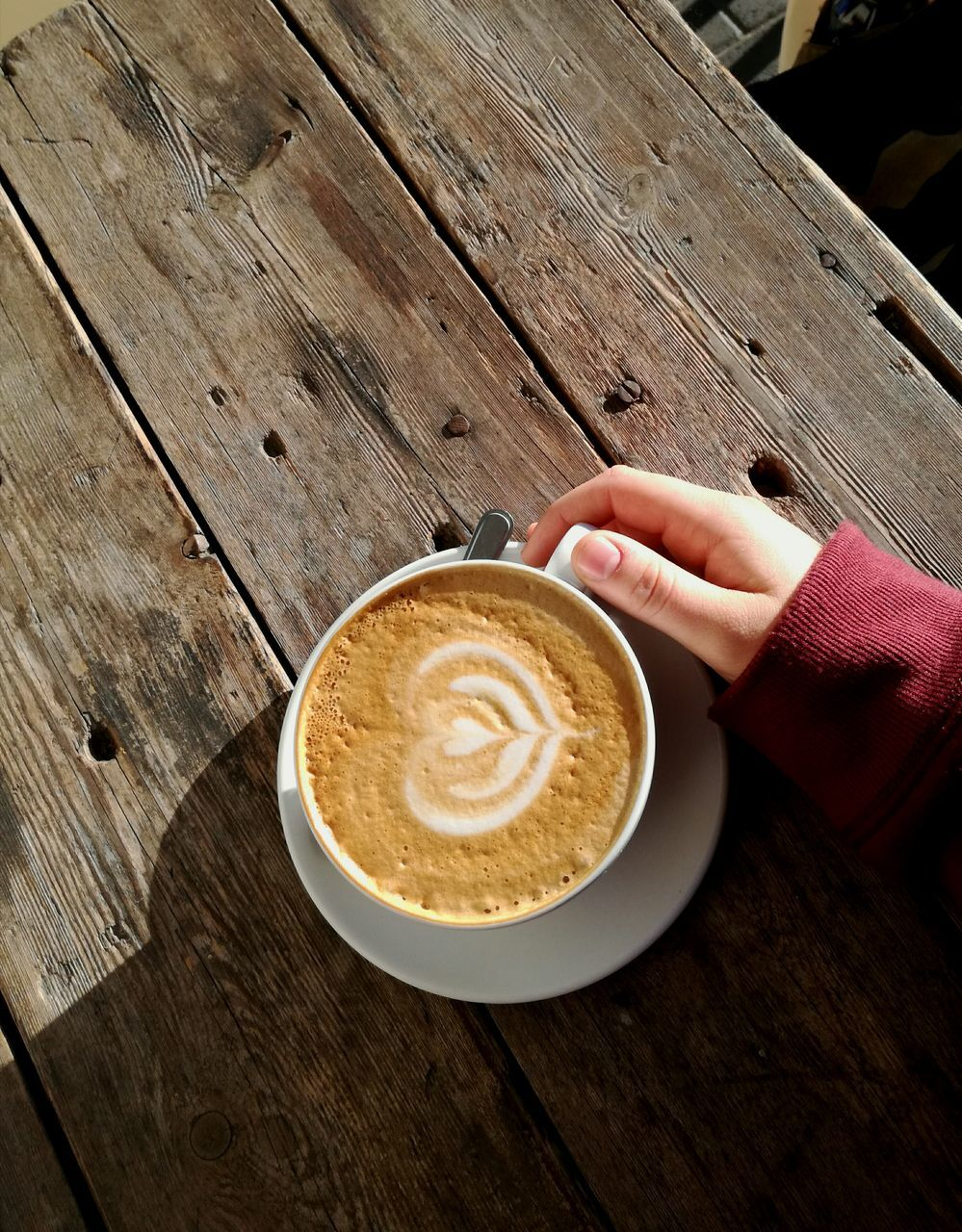 coffee - drink, human hand, coffee cup, drink, food and drink, refreshment, frothy drink, human body part, one person, table, froth art, real people, cappuccino, latte, holding, wood - material, cafe, indoors, saucer, freshness, lifestyles, close-up, women, day, mocha, people