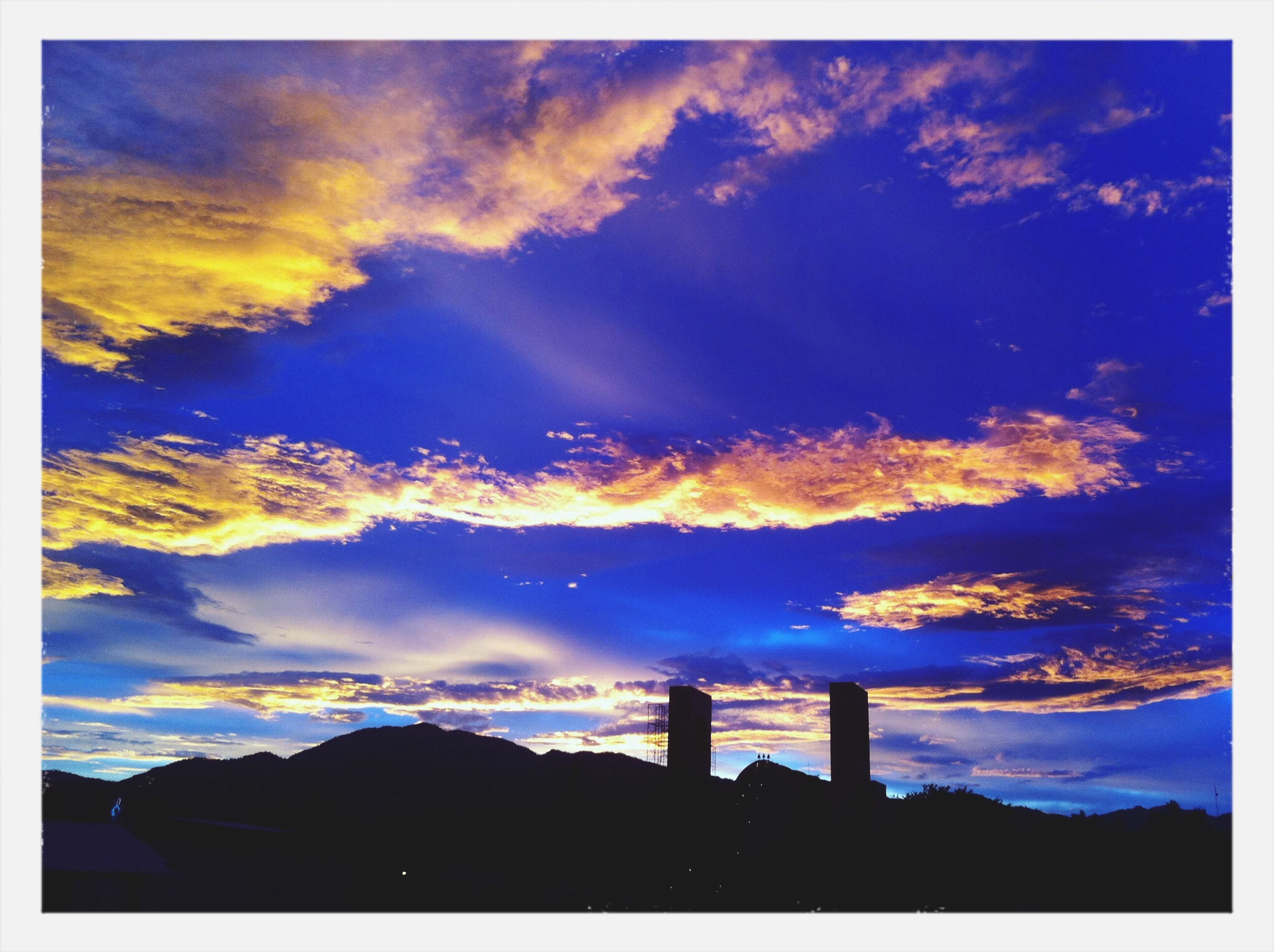 transfer print, silhouette, sunset, sky, auto post production filter, cloud - sky, beauty in nature, low angle view, scenics, built structure, cloud, building exterior, architecture, nature, tranquil scene, cloudy, tranquility, blue, dramatic sky, outline