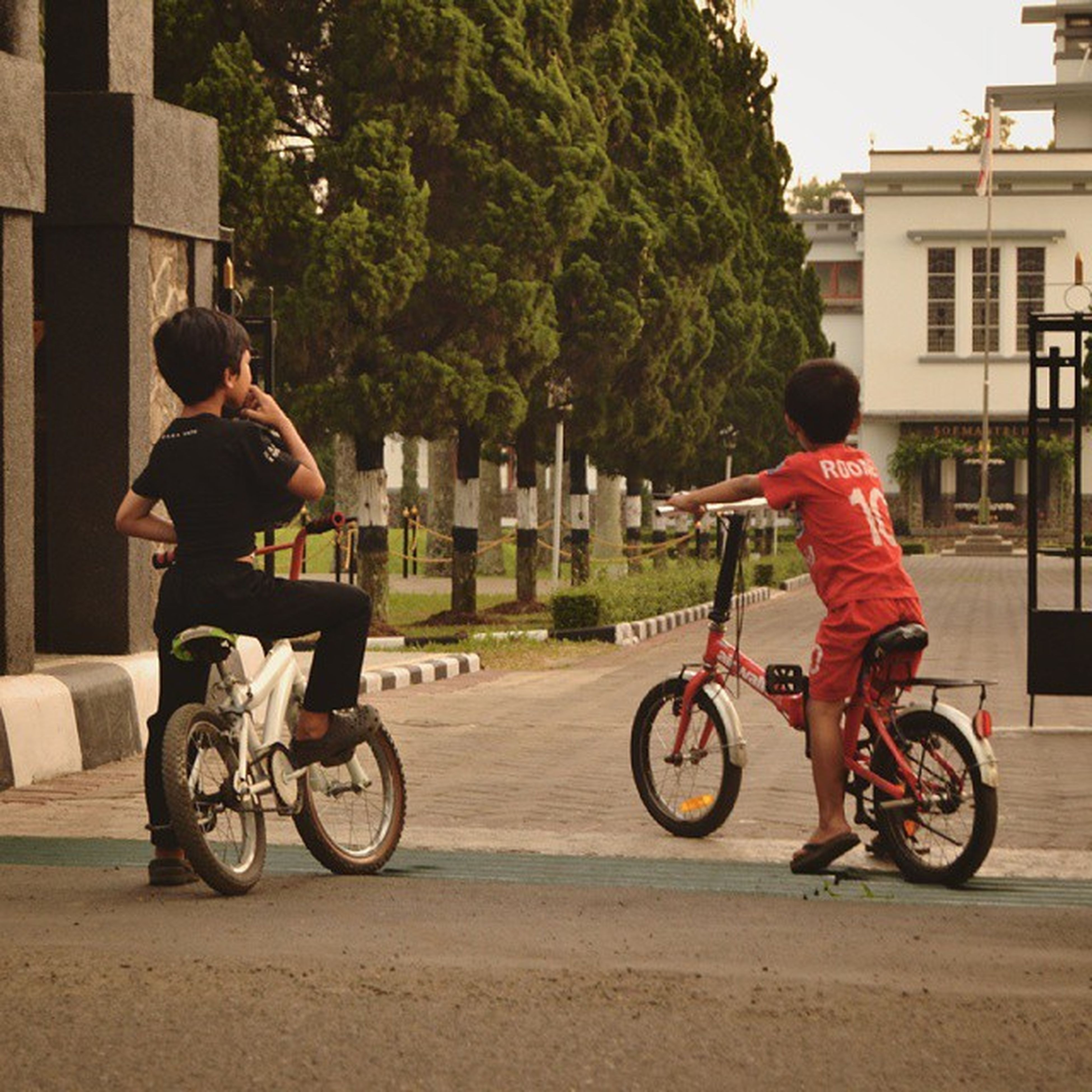 full length, bicycle, lifestyles, casual clothing, leisure activity, land vehicle, boys, transportation, childhood, mode of transport, girls, building exterior, person, riding, elementary age, street, togetherness