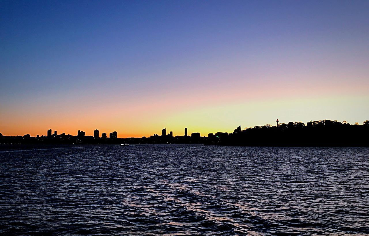 sunset, silhouette, copy space, clear sky, waterfront, no people, water, skyscraper, cityscape, nature, architecture, outdoors, building exterior, tranquil scene, beauty in nature, city, scenics, tranquility, sea, travel destinations, built structure, urban skyline, sky, day