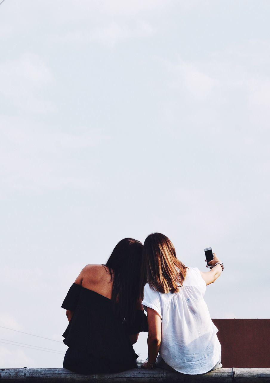 Rear View Of Women Taking A Selfie