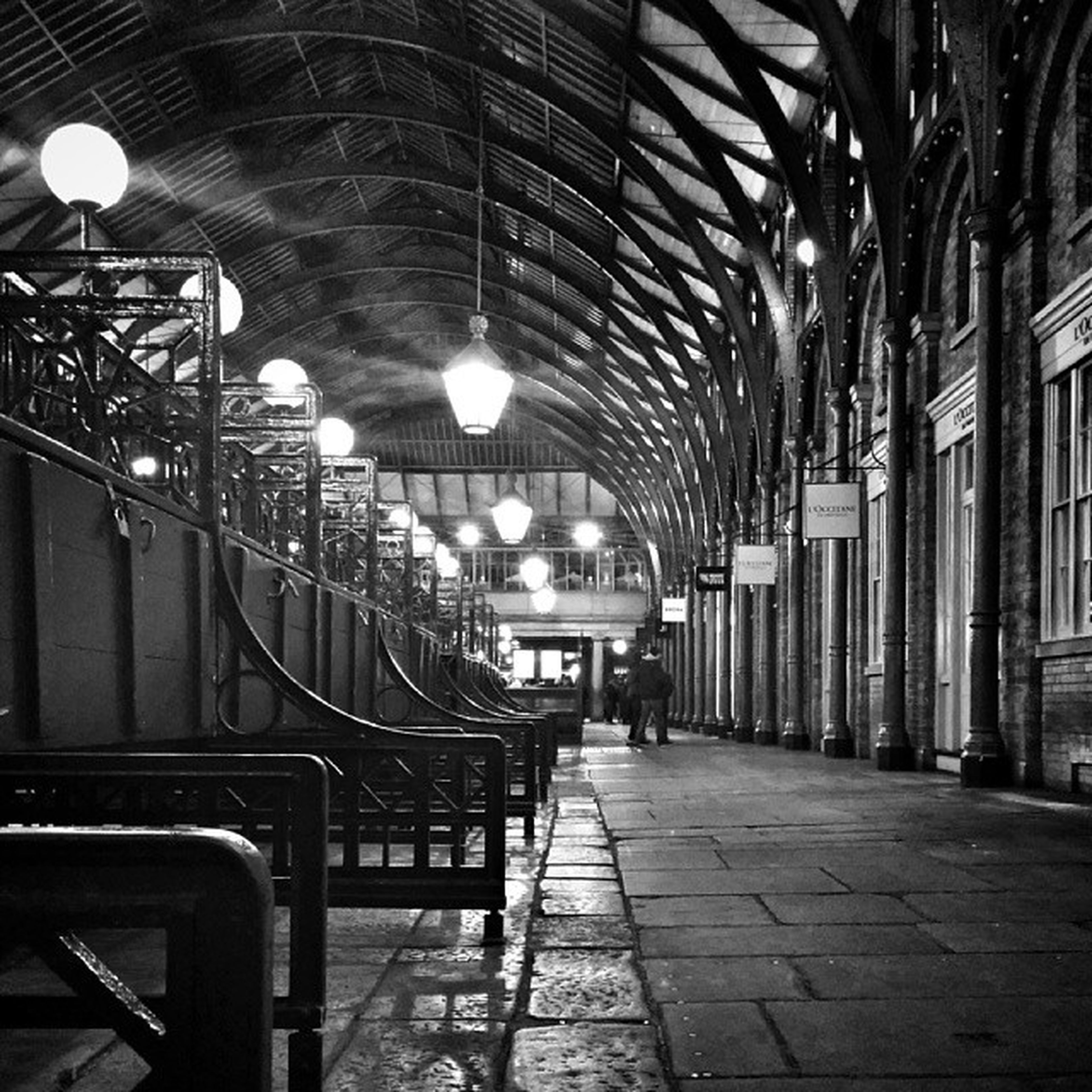 architecture, built structure, building exterior, the way forward, illuminated, lighting equipment, city, incidental people, transportation, street light, diminishing perspective, city life, street, vanishing point, in a row, night, building, person, mode of transport, cobblestone