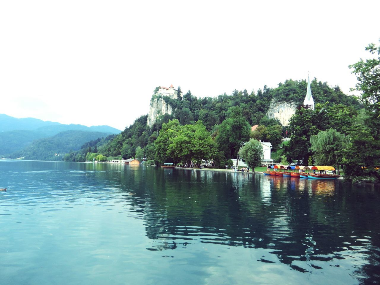 water, tree, mountain, lake, clear sky, nature, waterfront, day, beauty in nature, outdoors, scenics, sky, built structure, real people, architecture
