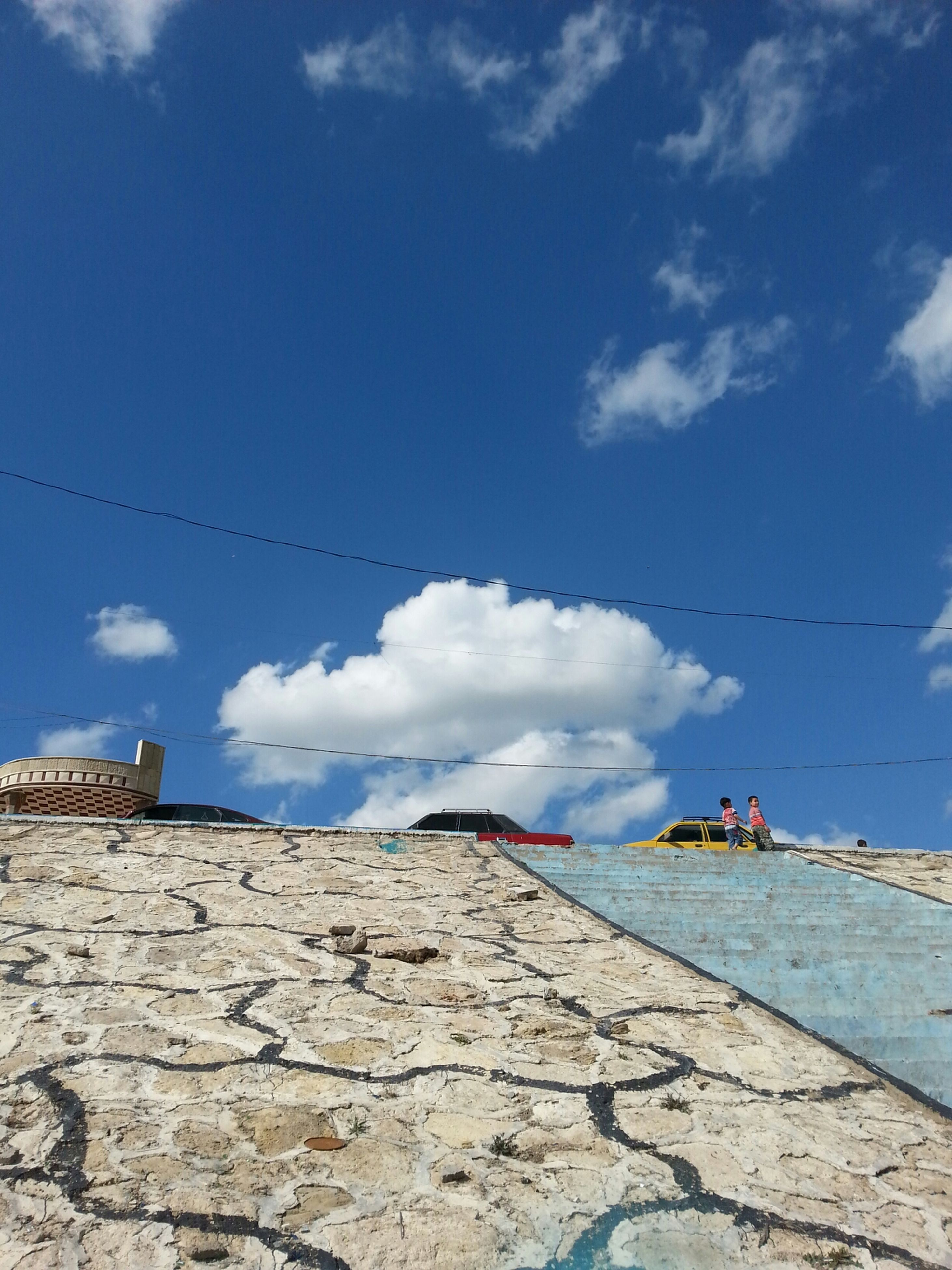 sky, low angle view, blue, built structure, cloud - sky, architecture, building exterior, cloud, day, outdoors, sunlight, wall - building feature, bird, roof, no people, nature, cloudy, house, stone wall, wall