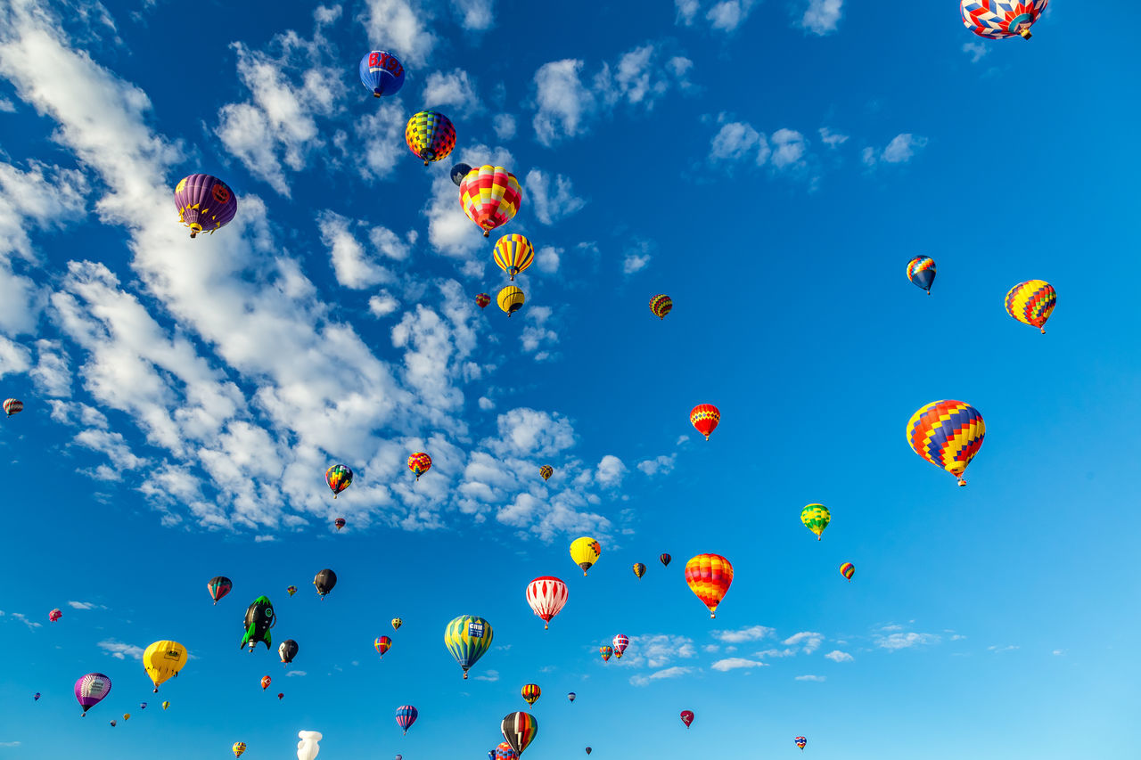 sky, low angle view, mid-air, balloon, celebration, large group of objects, multi colored, flying, ballooning festival, cloud - sky, outdoors, traditional festival, day, blue, no people, hot air balloon, nature