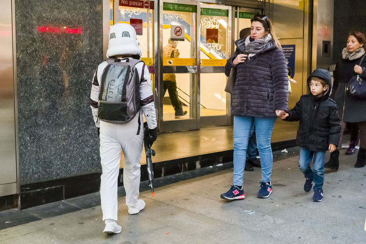 A young boy looking at a street performer dressed as storm trooper entering the Metro in Madrid. City City Life Metro Stormtrooper Adult Boys Candid Childhood Day Editorial  Expression Full Length Leisure Activity Lifestyles Men Outdoors People Real People Standing Togetherness