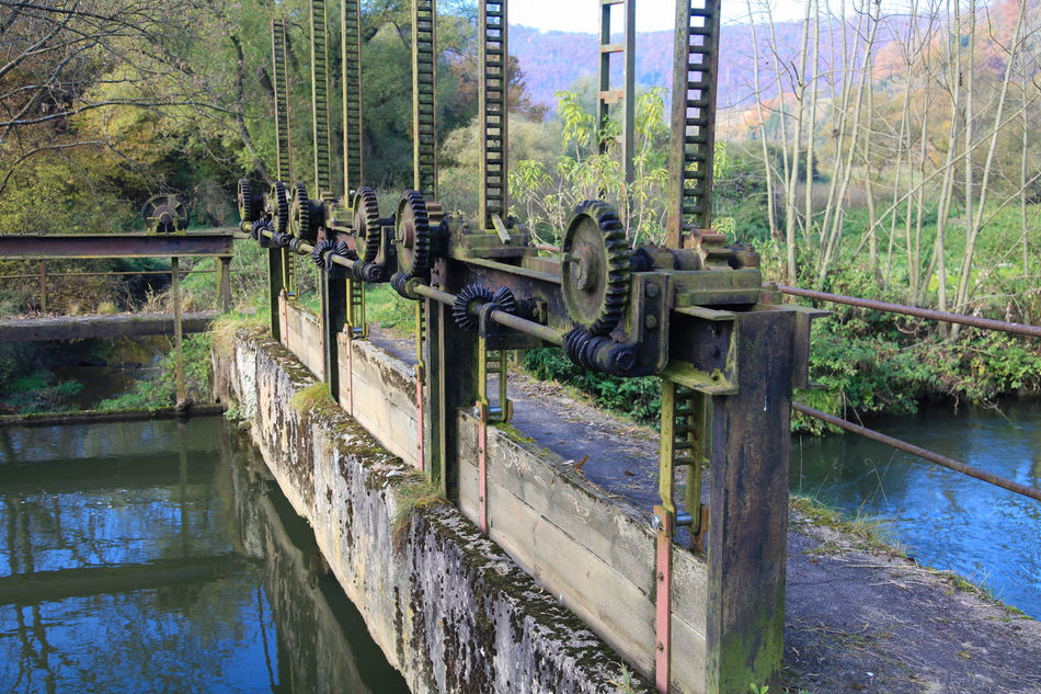 River and old weir Alternative Energy Architecture Canal Cogwheel Dam Flood Floodgate Gate Industry Iron Landscape Metal Nature No People Old Outdoors Power Generation Protection River Rust Sky Technology Tree Water Weir