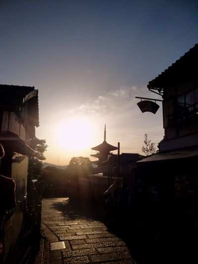 The sun turning the pagoda into a silhouette Sunlight And Shadow Ultimate Japan Pagoda City Life Kyoto LenseFlare Silhouette Bright The Way Forward Building Exterior Sunbeam Nature Street Empty Residential District Mountains Tree Clouds The City Light