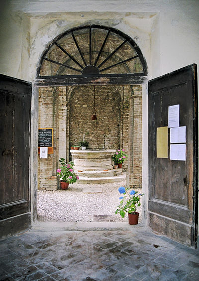 A doorway in a street in Tuscany opens to a lane with pots of flowers. Ancient Architecture Architecture Built Structure Cobblestone Day Doorway Flower Gate Italian Light And Shadow No People Outdoors Pathway Pots Of Flowers Public Notice Stone Wall Sunlight The City Light Town Wood - Material Well  Mobile Conversations