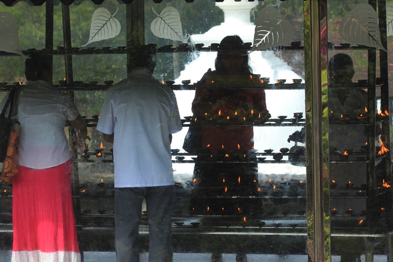 Buddhism Casual Clothing Day Devotion Flames Kandy_town Man Reflection Religion Silhouette Sri Lanka Temple Votive Offers Women