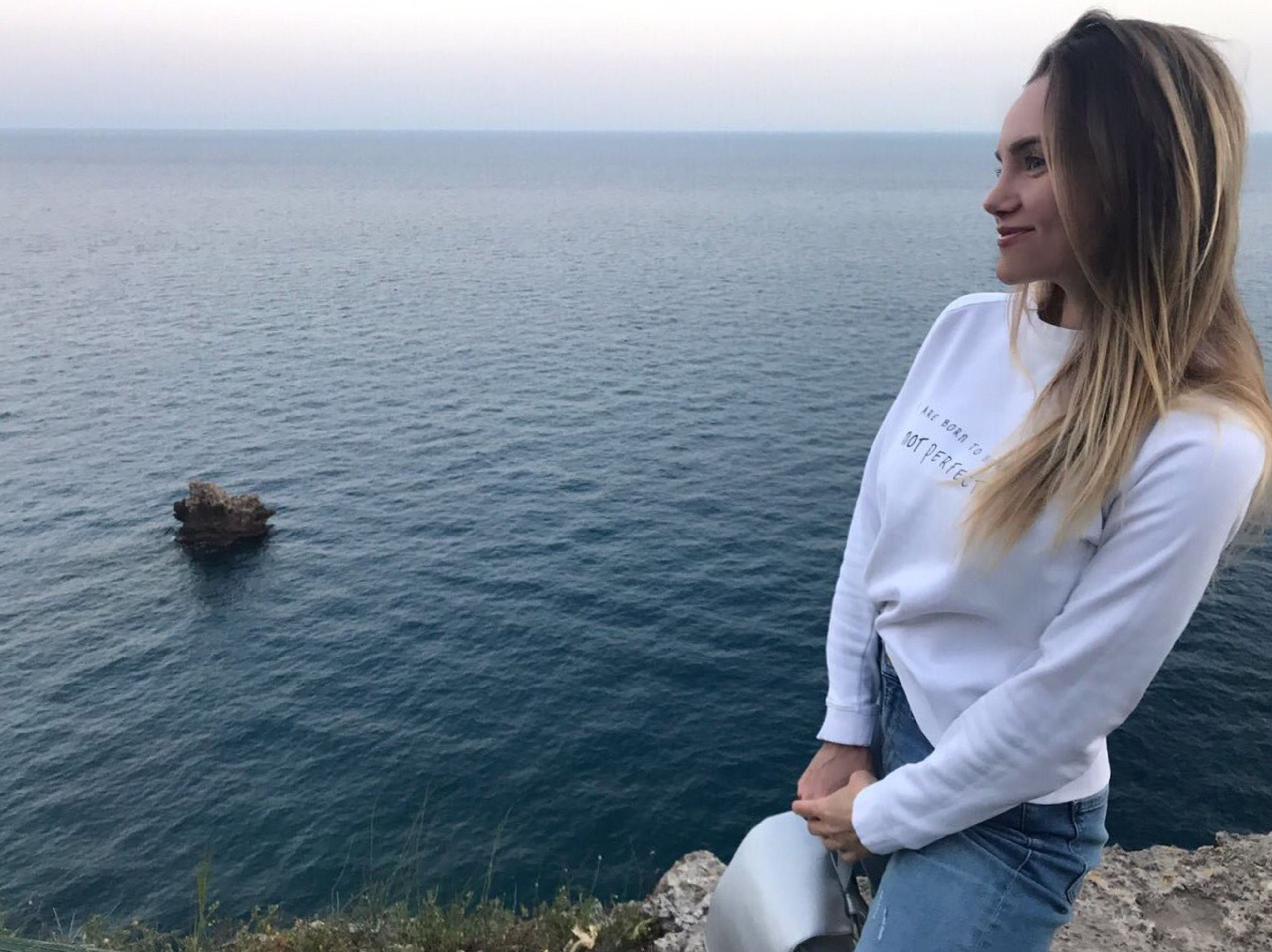 sea, one person, water, real people, nature, leisure activity, outdoors, day, young adult, beach, casual clothing, horizon over water, young women, standing, tranquility, lifestyles, relaxation, vacations, sitting, blond hair, beauty in nature, sky, people