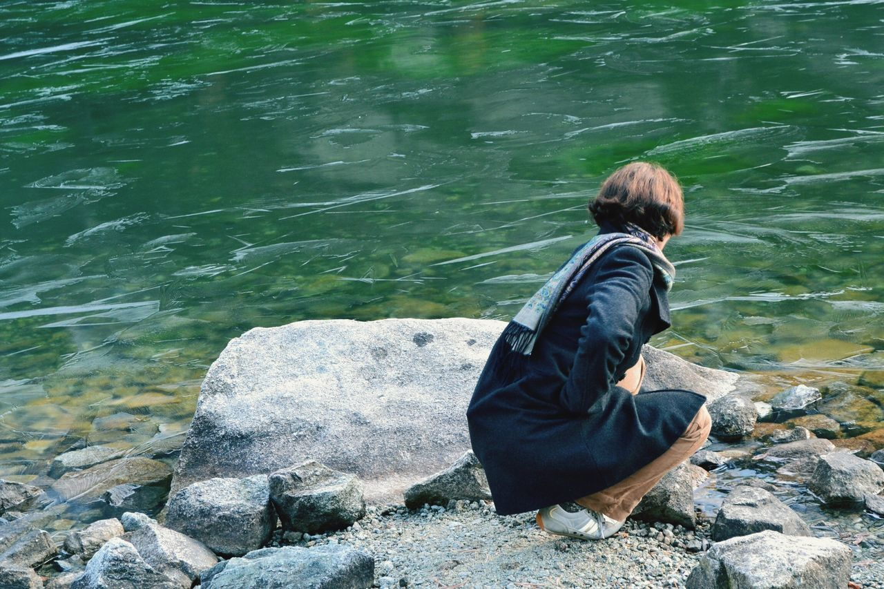 Woman Crouching On Rock At Seaside