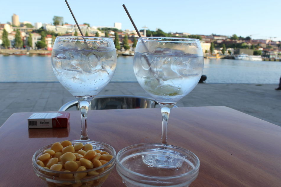 summer chill. 🍹🌅 Alcohol Cocktail Day Douro  Douro River Drink Food And Drink Gin And Tonic Lupin Bean Marlboro Red No People Outdoors Porto Portugal Pub River Summer Table Tremoços