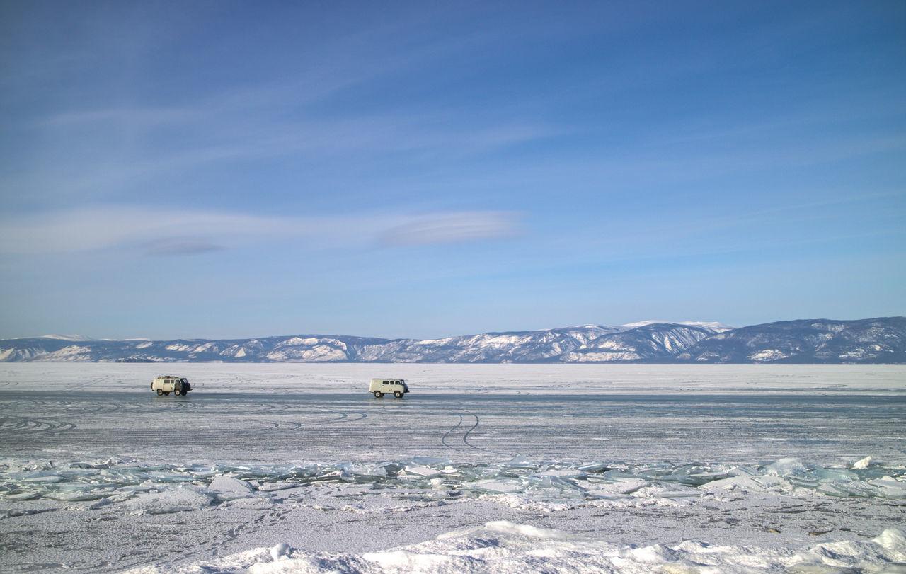 Vans On Frozen Lake Baikal Against Sky