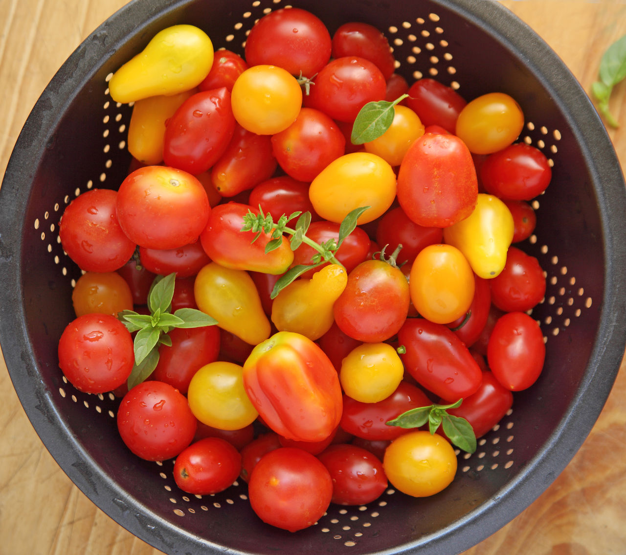 Cherry tomatoes in a dark colander Fresh Produce Natural Light Pear Tomatoes Red Cherry Tomatoes Close-up Colander Colorful Day Food Fresh Herbs  Harvest Healthy Eating Indoors  Leaves Many No People Overhead Seasonal Summer Variety Yellow