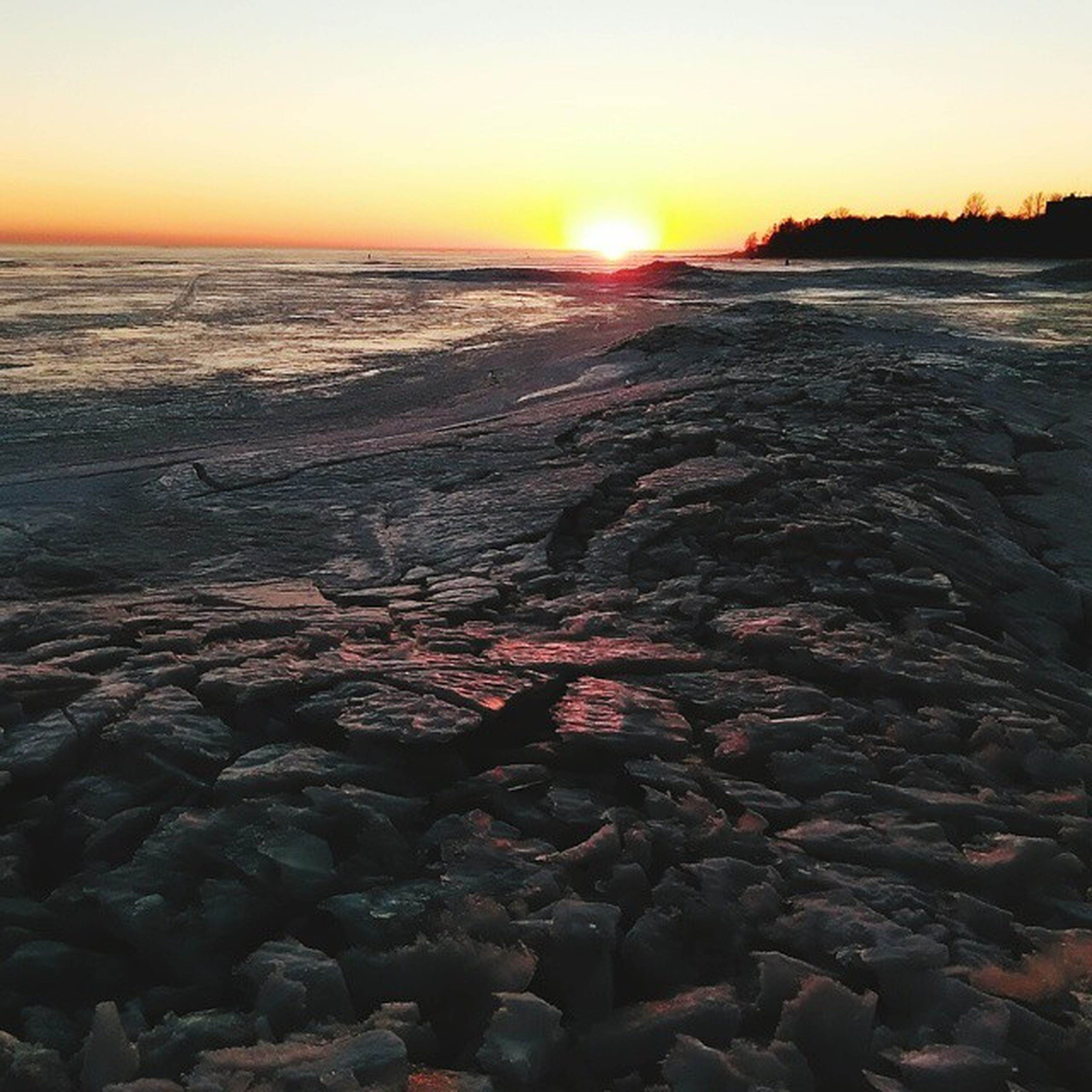 sunset, sun, water, sea, scenics, tranquil scene, tranquility, beach, beauty in nature, orange color, nature, horizon over water, sky, shore, idyllic, sunlight, rock - object, reflection, stone - object, outdoors