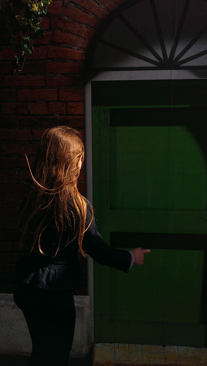 Rear View Of Girl Pointing At Closed Door