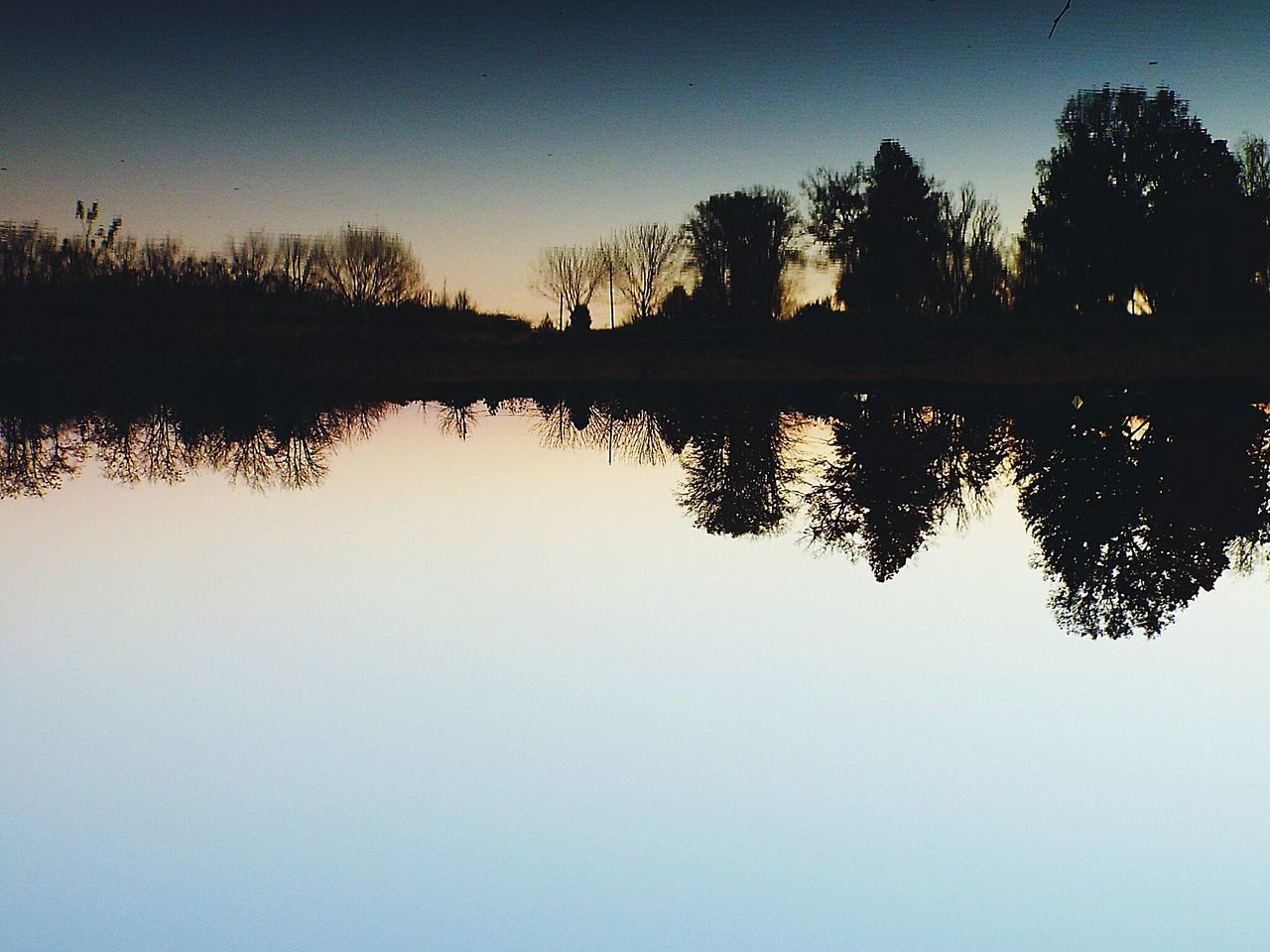 Reflection Of Silhouette Trees On Calm Lake Against Clear Sky During Sunset