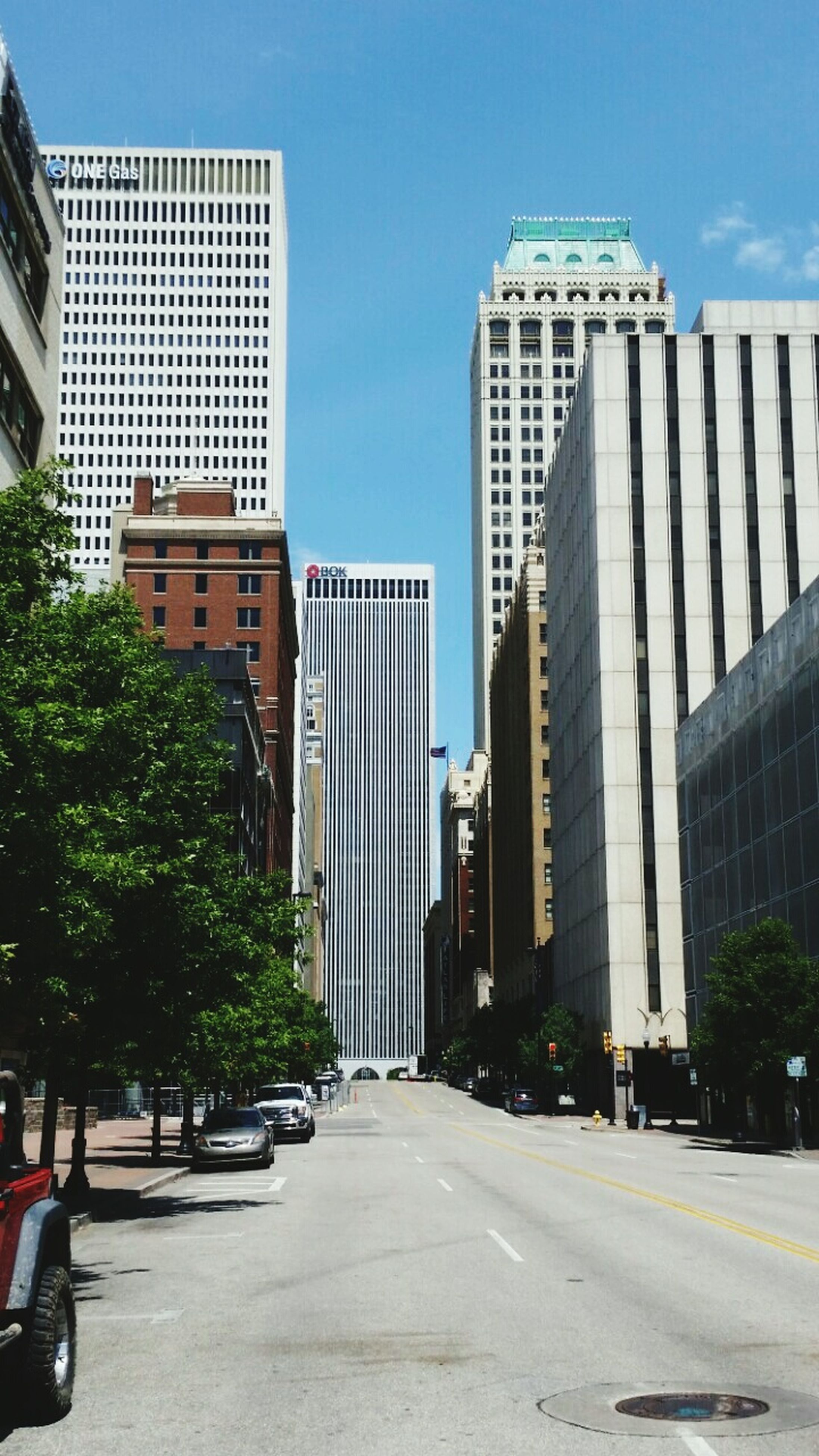 architecture, building exterior, built structure, city, skyscraper, modern, tall - high, office building, tower, tree, transportation, the way forward, road, car, building, clear sky, blue, street, low angle view, sky