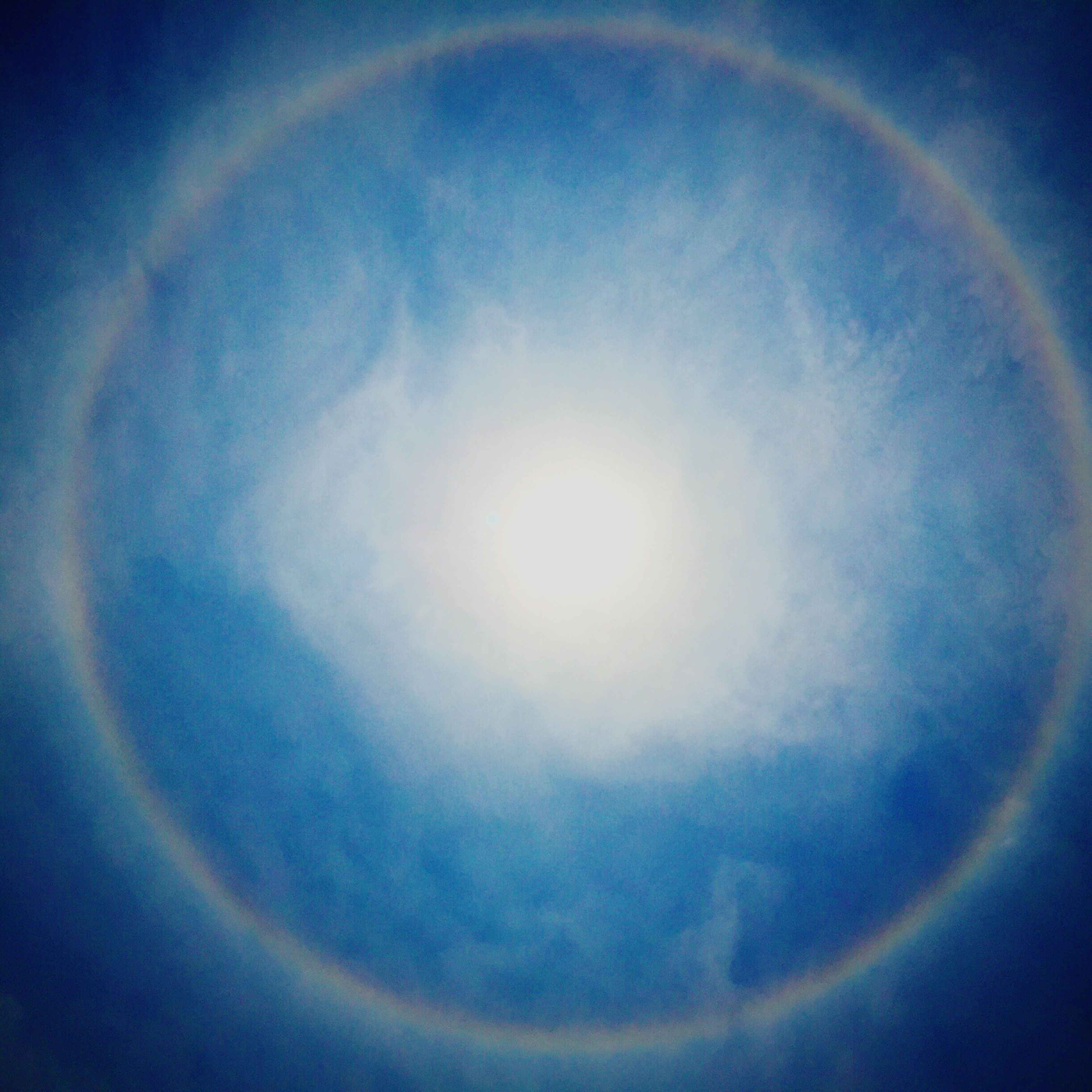 sky, low angle view, sky only, beauty in nature, scenics, cloud - sky, tranquility, blue, circle, moon, nature, tranquil scene, sun, idyllic, astronomy, majestic, cloud, planetary moon, no people, full moon