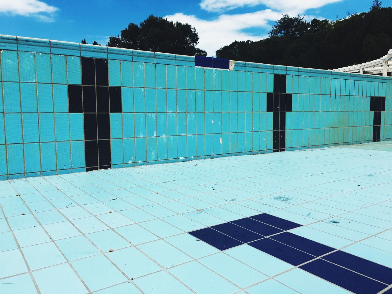 Empty swimming pool. Summertime nostalgia. Swimming Pool Sky Outdoors Tile Day No People Blue Tree Sport Competitive Sport Water Architecture Seaside_collection Tranquility Nostalgia Design Concrete Simple