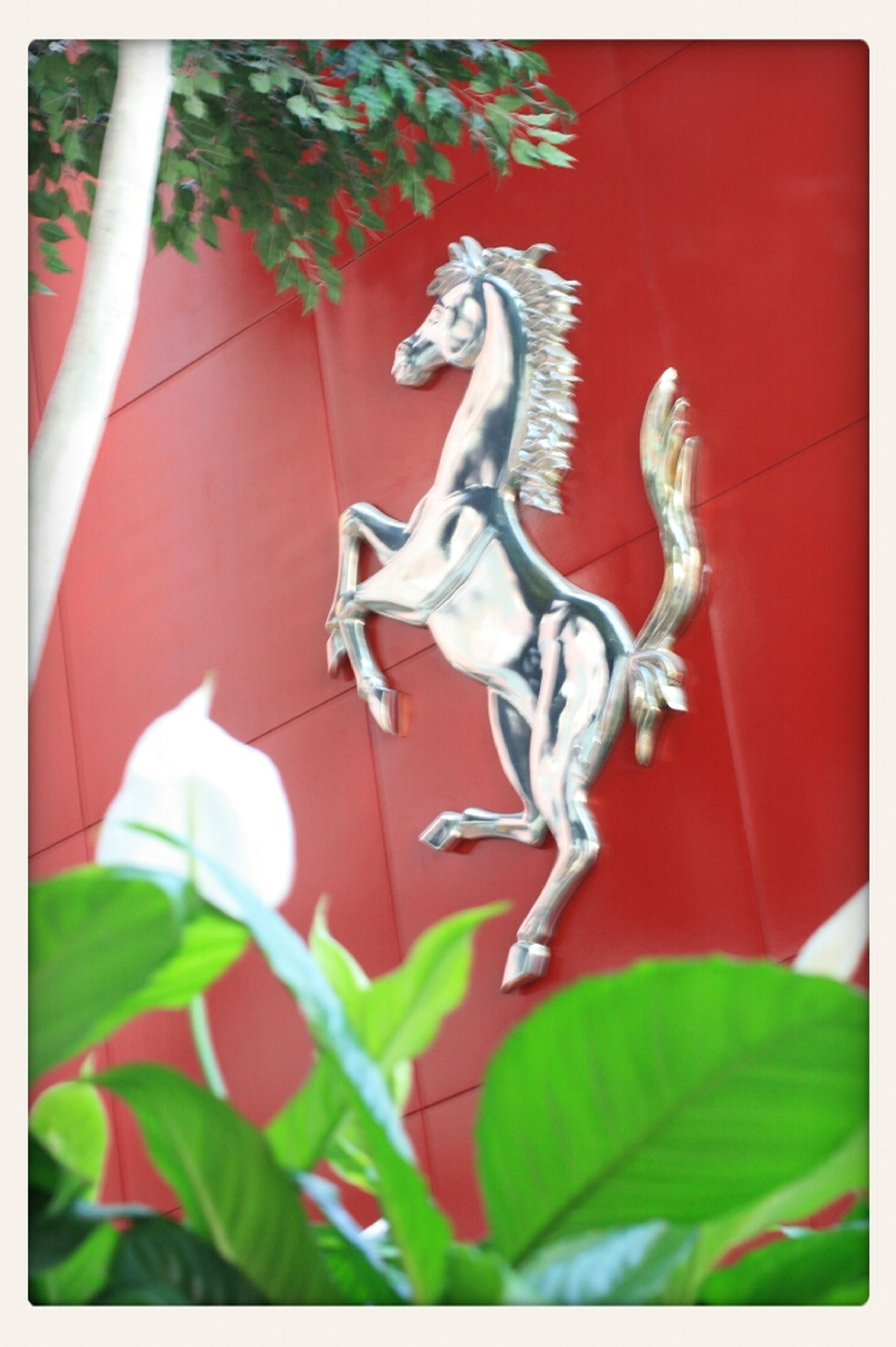 transfer print, auto post production filter, indoors, art and craft, art, creativity, animal representation, red, human representation, statue, sculpture, close-up, animal themes, day, wall - building feature, no people, sunlight, one animal, plant