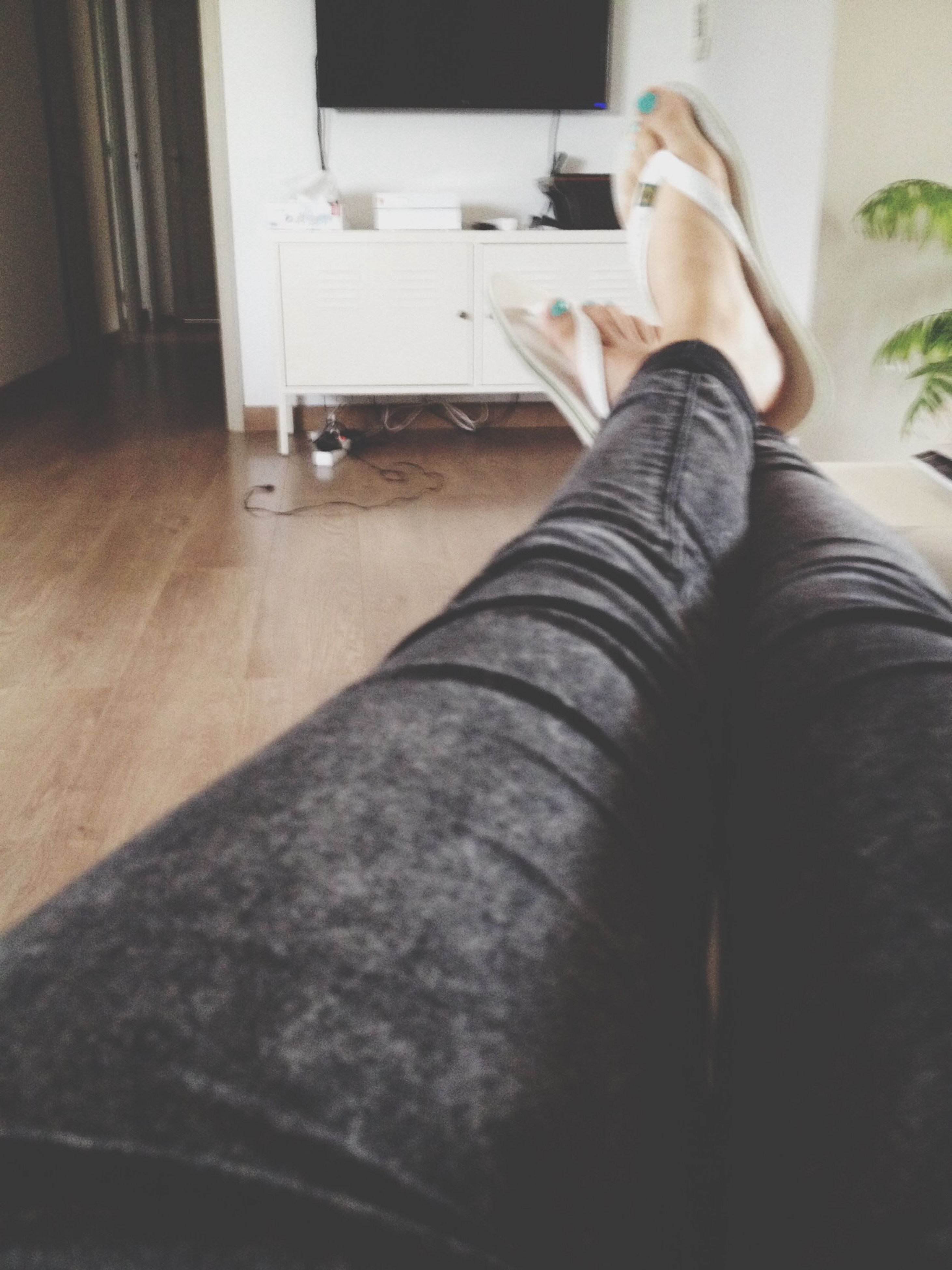 low section, person, indoors, lifestyles, sitting, shoe, leisure activity, human foot, standing, relaxation, home interior, personal perspective, casual clothing, barefoot, flooring, legs crossed at ankle