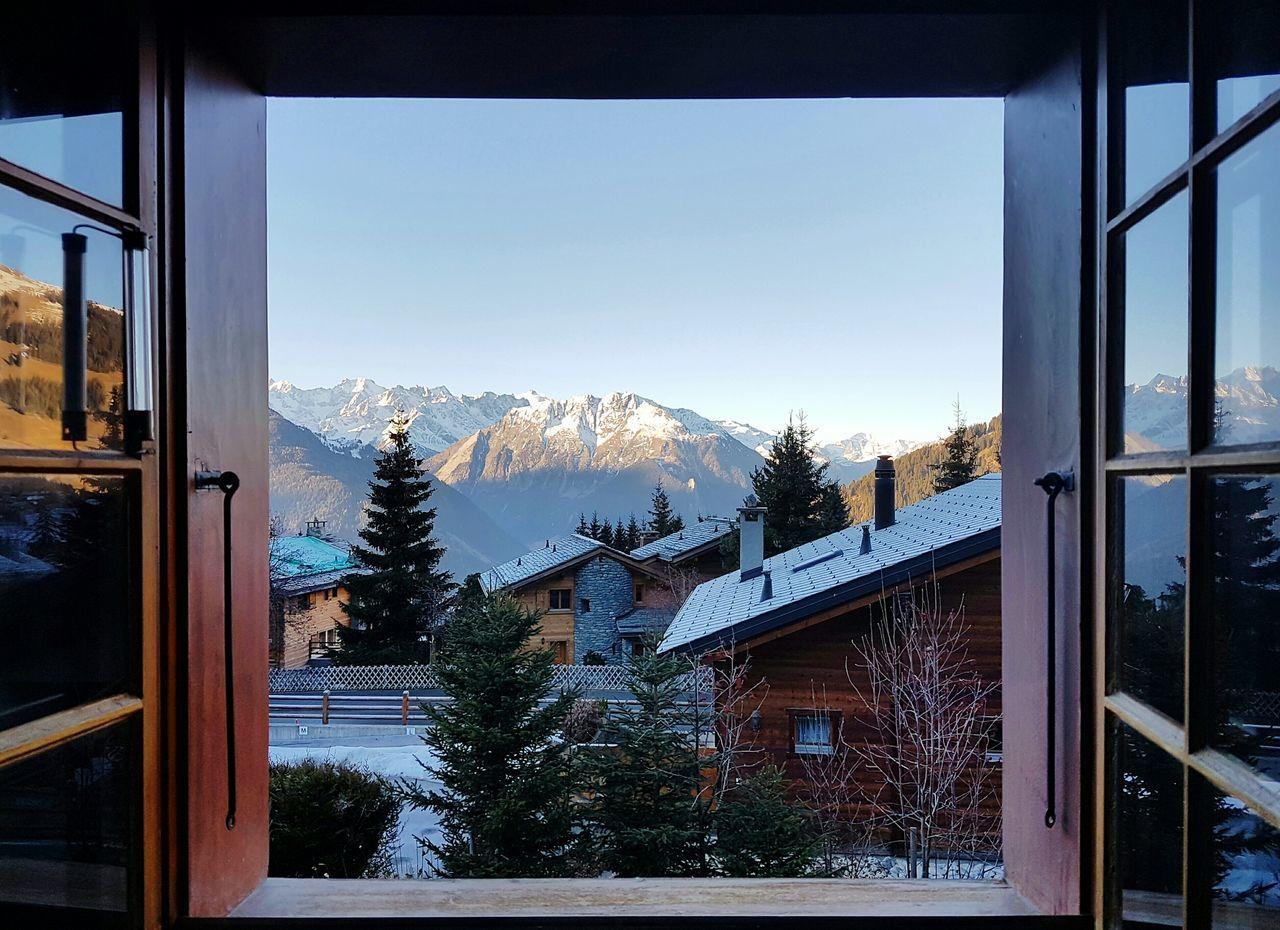 Breathtaking Switzerland. AlpsMountain Snow Chalet Verbier Mountains And Sky Looking Through Window Morning Views