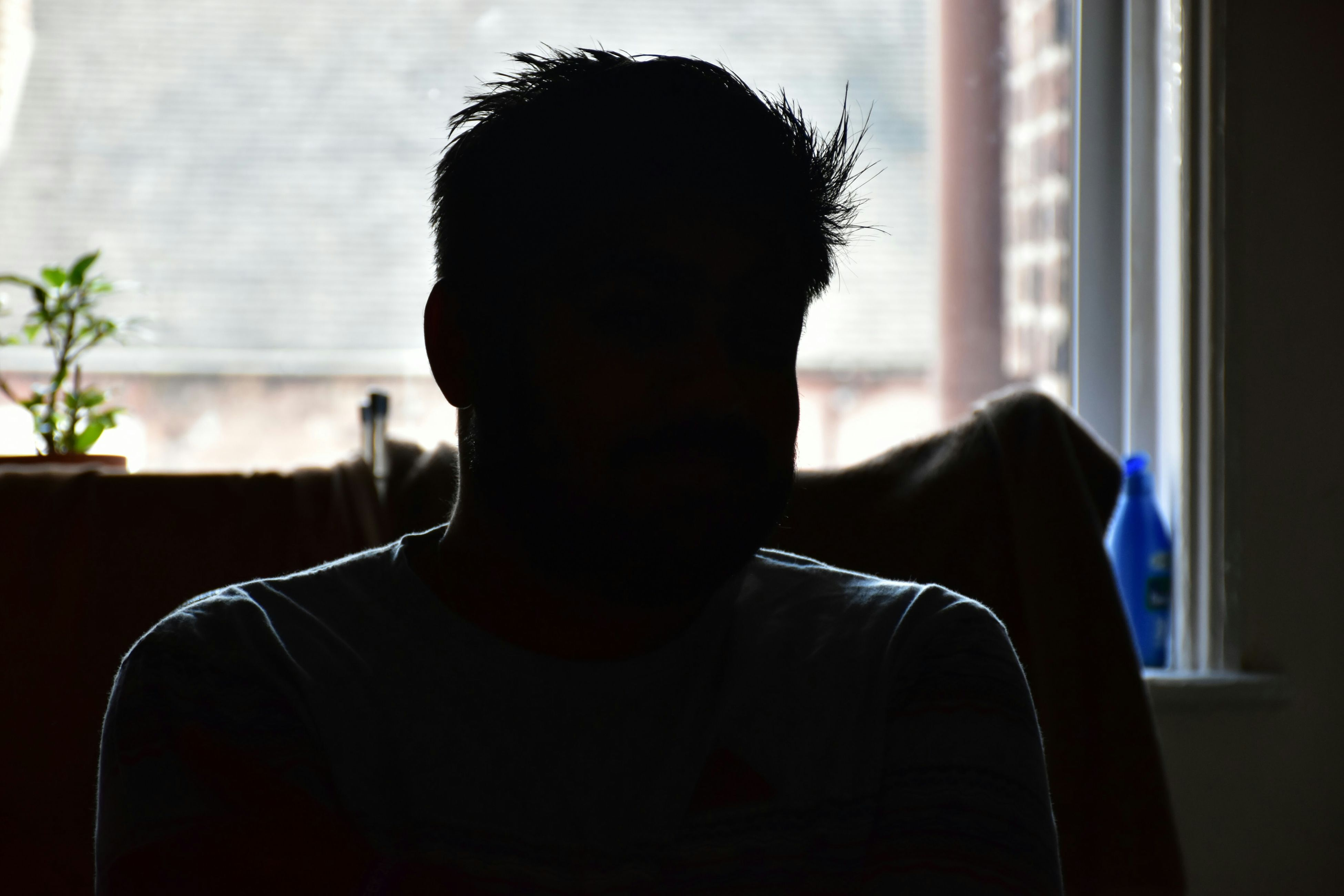 indoors, window, relaxation, sitting, lifestyles, rear view, silhouette, home interior, side view, leisure activity, person, sunlight, focus on foreground, day, men, sofa, looking through window, resting