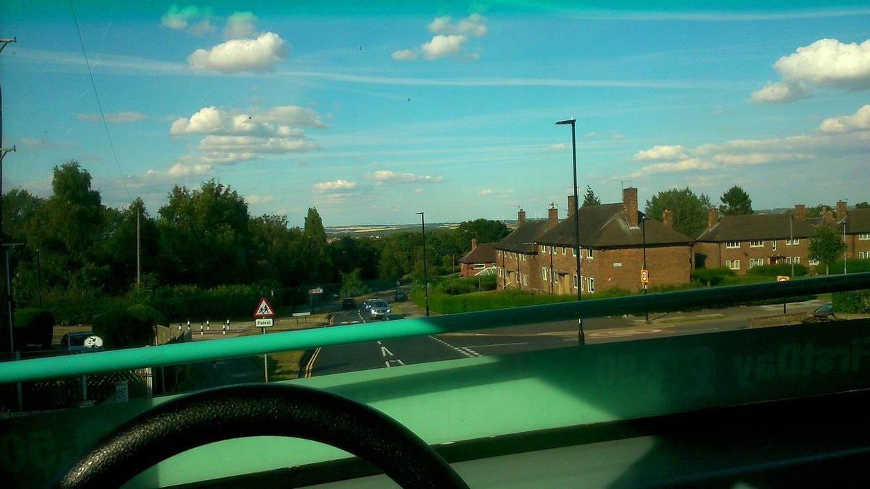 Top of double decker bus. Bus First Houses Road Scenery View Cars Clouds And Sky