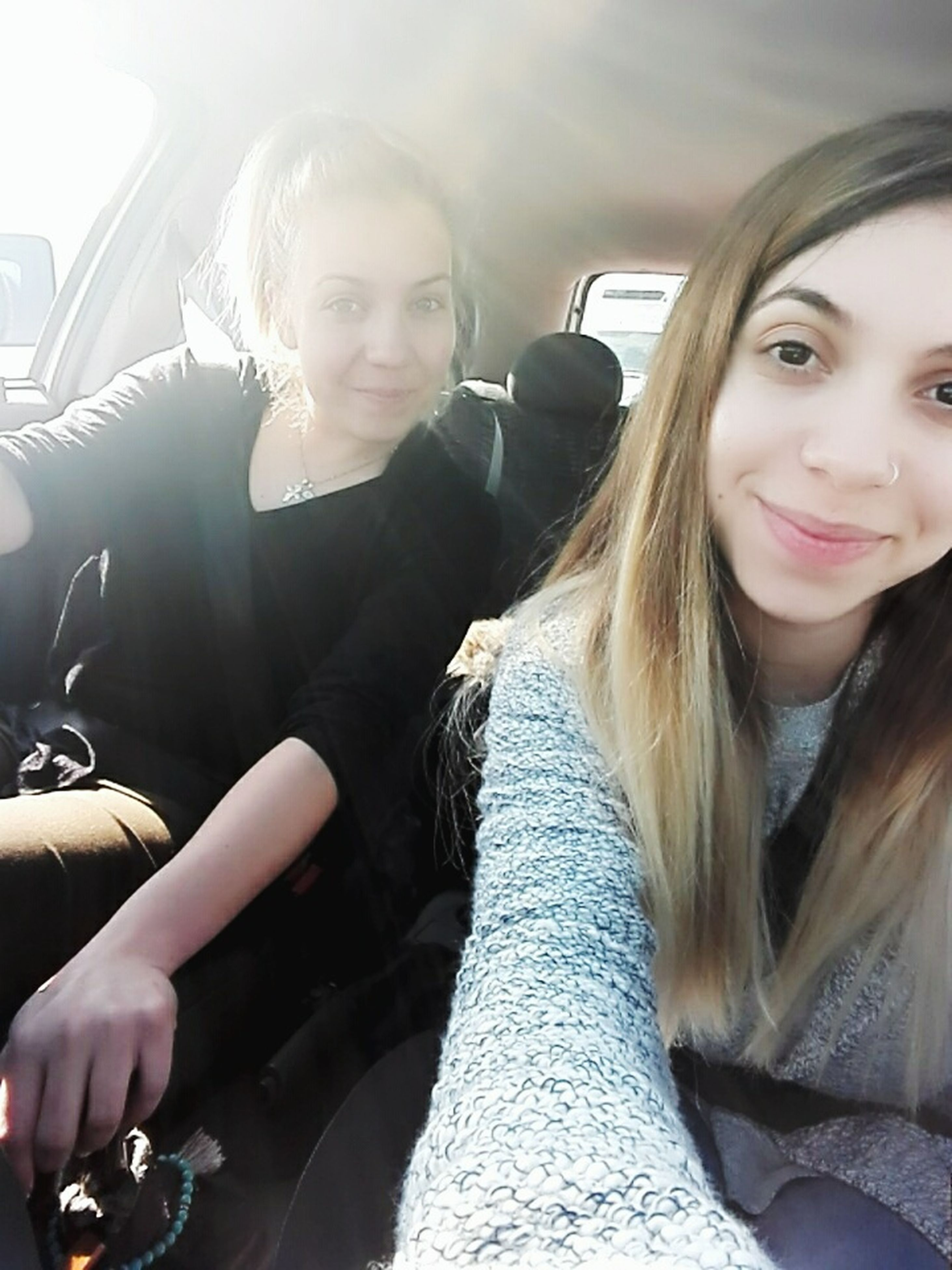 sitting, two people, young women, young adult, togetherness, car, looking at camera, women, vehicle interior, transportation, portrait, adult, beauty, beautiful woman, people, car interior, friendship, smiling, happiness, bonding, adults only, human leg, indoors, day, fame