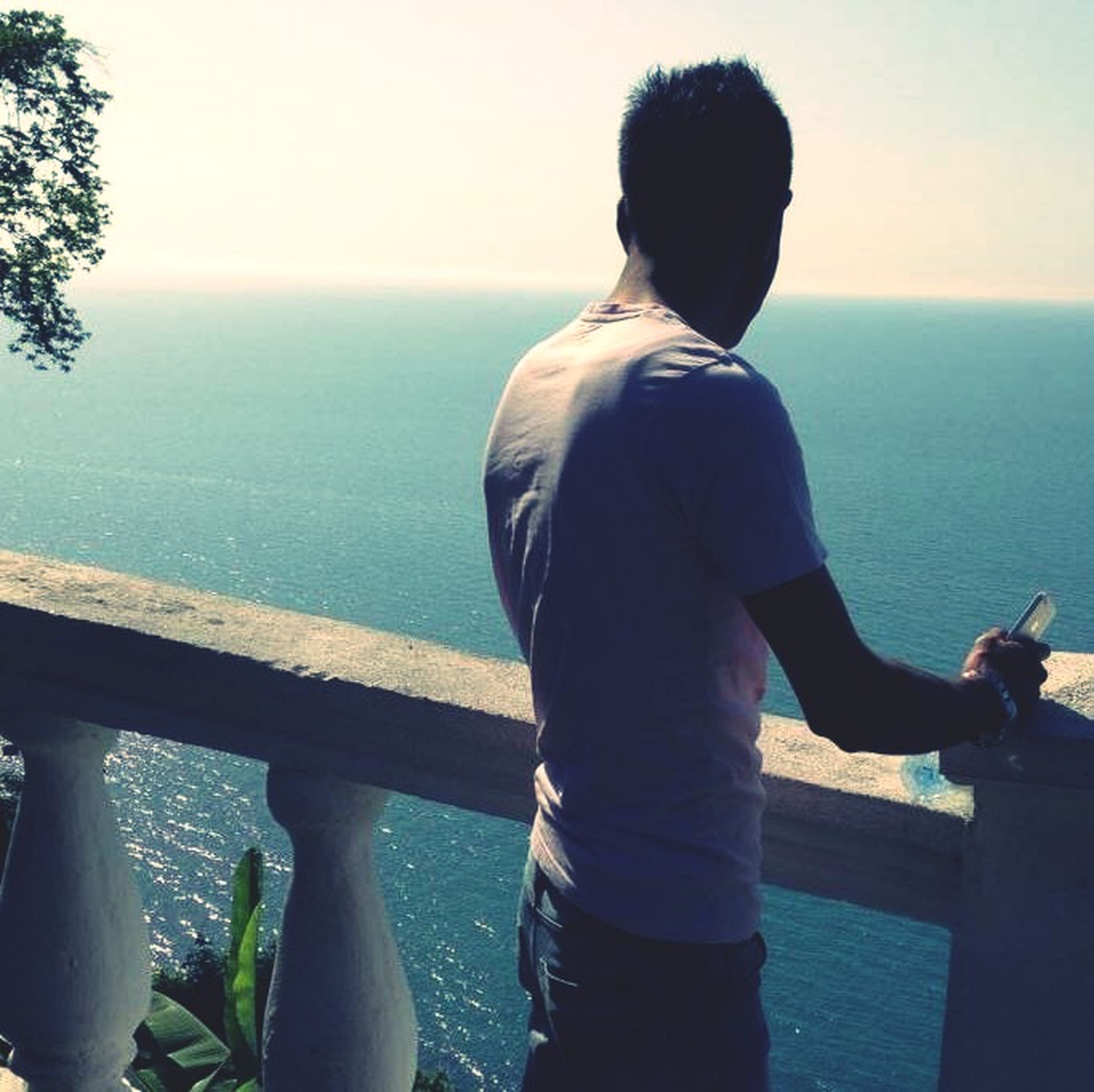 sea, horizon over water, rear view, water, lifestyles, leisure activity, railing, looking at view, standing, sky, clear sky, men, person, scenics, tranquil scene, tranquility, casual clothing, beauty in nature