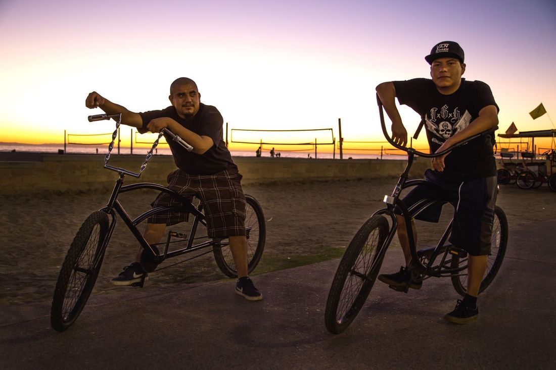 """Embrace Diversity Series: As we were leaving Huntington beach, after another amazing sunset, we came upon these fellas. I told them that they looked """"badass"""" & asked if I could take their photo, just as they were on their low riders. They agreed & afterward I introduced myself & connected with one of them on Instagram. I'm stoked by the diversity of cultures, colors, & backgrounds in SoCal. Embrace diversity. Embrace Diversity Huntingtonbeach Huntington Beach Beach Beachphotography Beach Photography Streetphotography Street Photography Streetphoto_color Street Portrait Street Portraits Sunset Sunsets Sunset_collection Bike Bikers Low Rider  The Photojournalist - 2016 EyeEm Awards People Of The Oceans Original Experiences Two Is Better Than One CyclingUnites"""