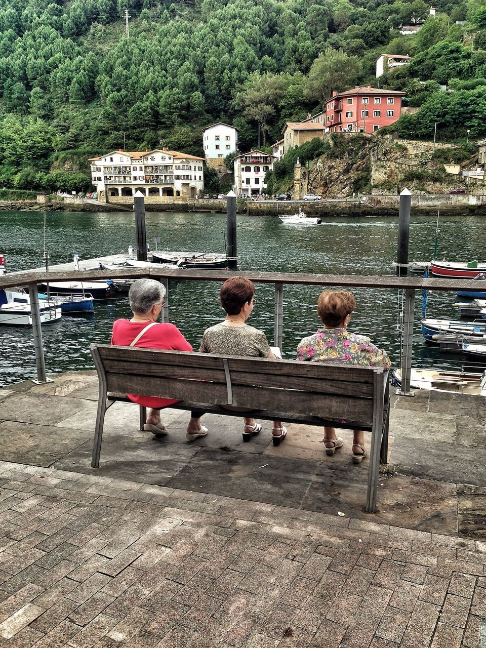 View Of Three Senior Women Sitting On Bench At Riverfront