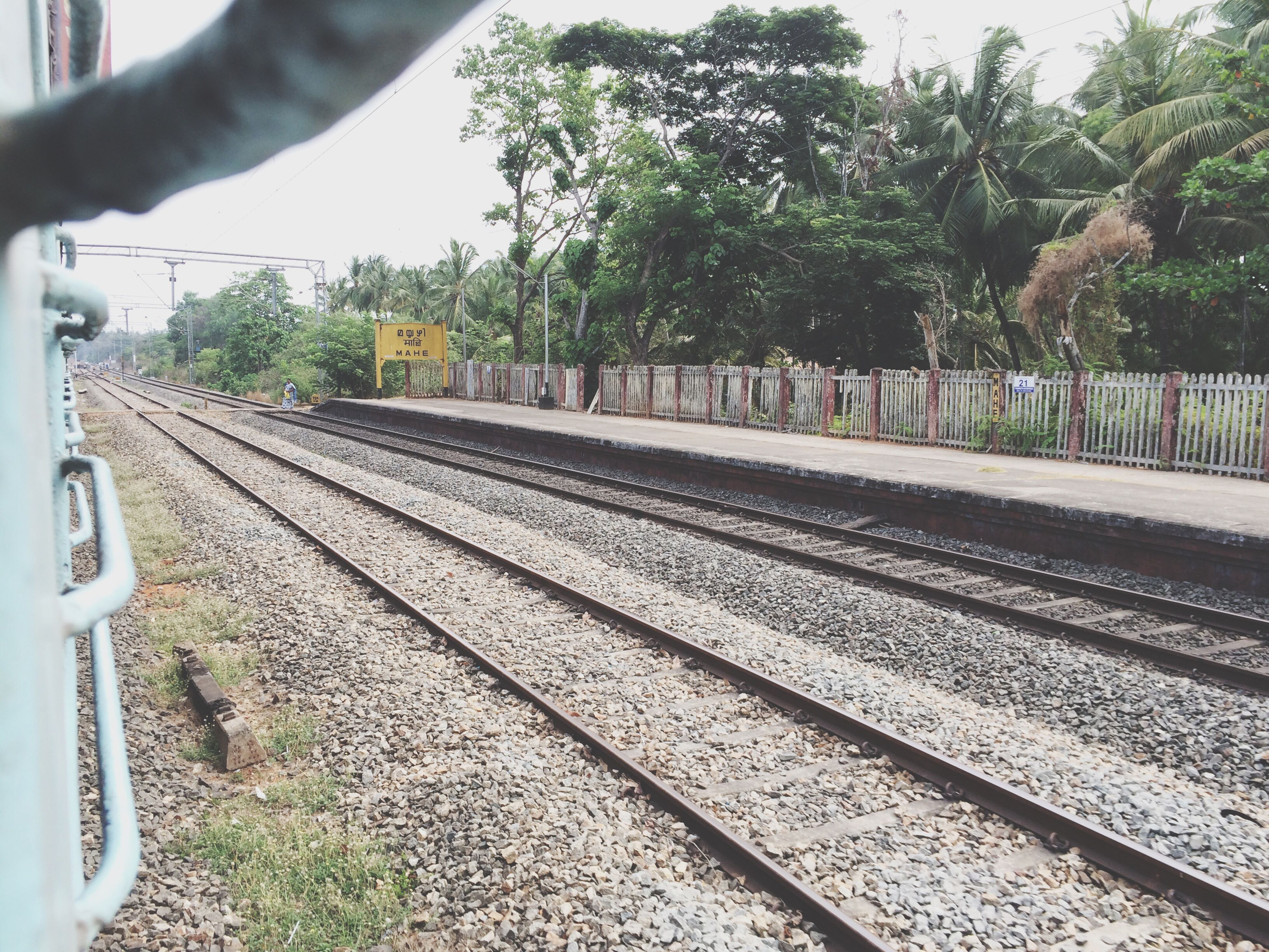 railroad track, transportation, rail transportation, tree, public transportation, railroad station platform, the way forward, diminishing perspective, railroad station, railway track, mode of transport, train - vehicle, vanishing point, day, travel, train, outdoors, no people, road, sky
