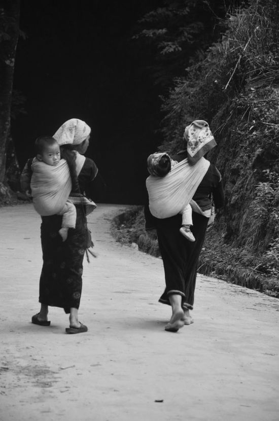 Pu'er China Yunnan Ethnic Minorities Rural two young Miao minority mother's with their children strapped to their backs walking to the village market