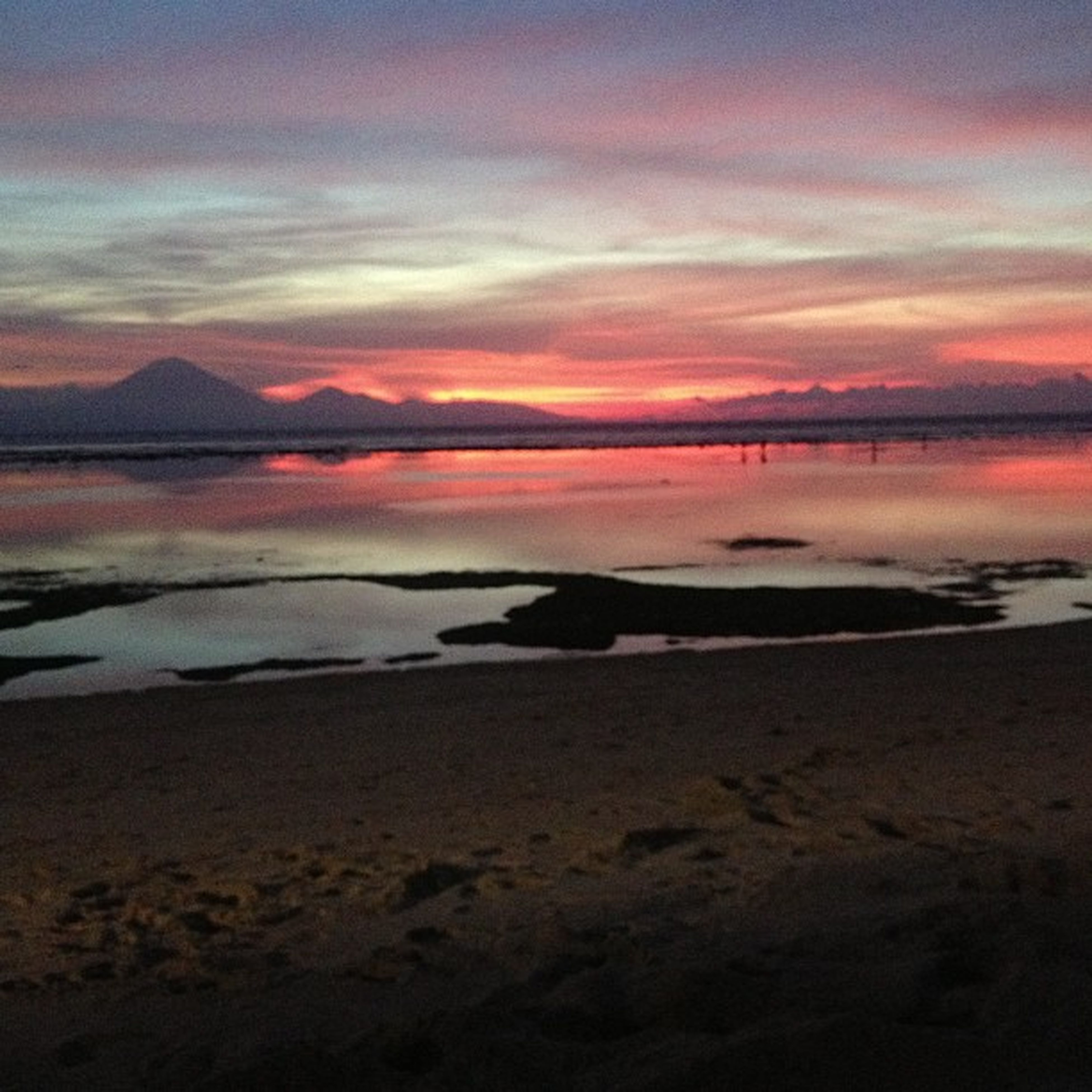 sunset, water, scenics, tranquil scene, sea, sky, beach, beauty in nature, tranquility, orange color, mountain, shore, nature, idyllic, cloud - sky, silhouette, sand, dusk, coastline, outdoors