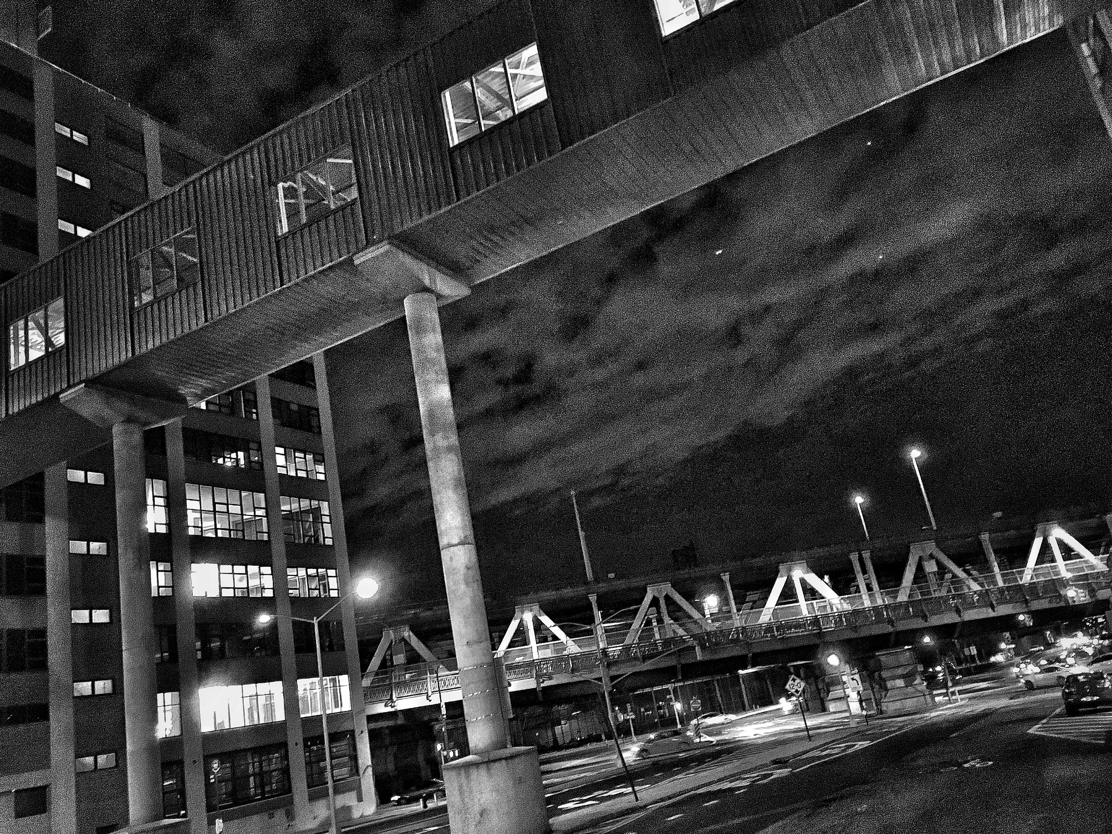 architecture, built structure, building exterior, night, city, bridge - man made structure, transportation, text, railing, western script, building, sky, low angle view, outdoors, connection, no people, street, communication, road, street light
