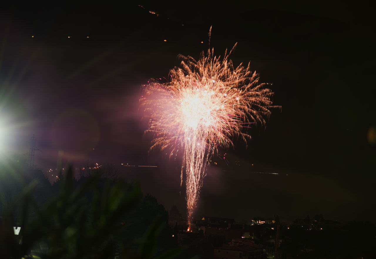 firework display, celebration, night, firework - man made object, exploding, long exposure, motion, arts culture and entertainment, event, blurred motion, low angle view, sky, illuminated, outdoors, firework, no people, multi colored, city
