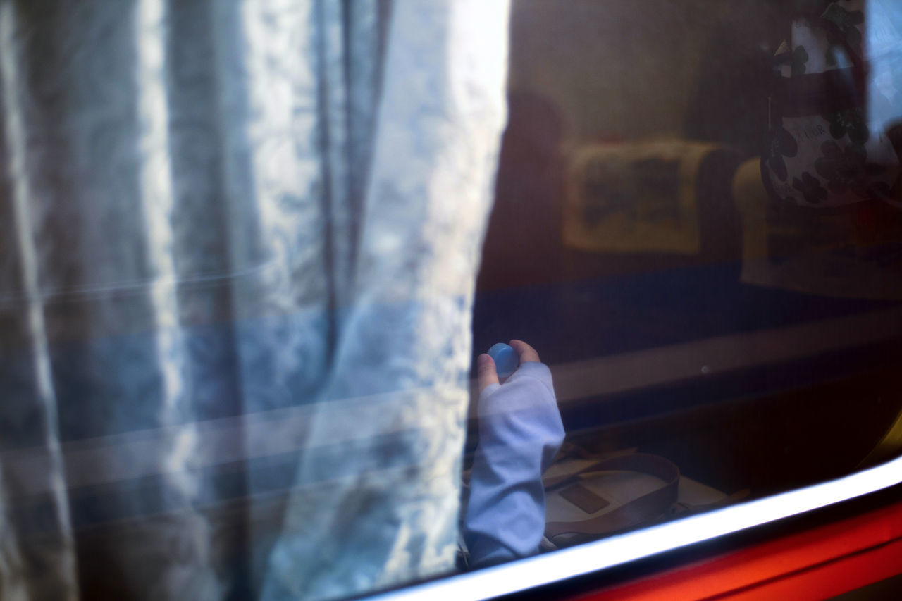 Cropped Image Of Hand Seen Through Train Window