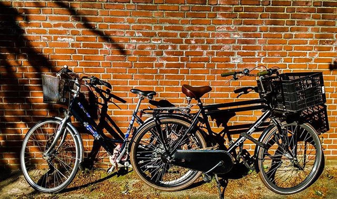 bicycle, brick wall, transportation, mode of transport, stationary, land vehicle, day, outdoors, bicycle rack, no people, architecture, built structure, sunlight, building exterior