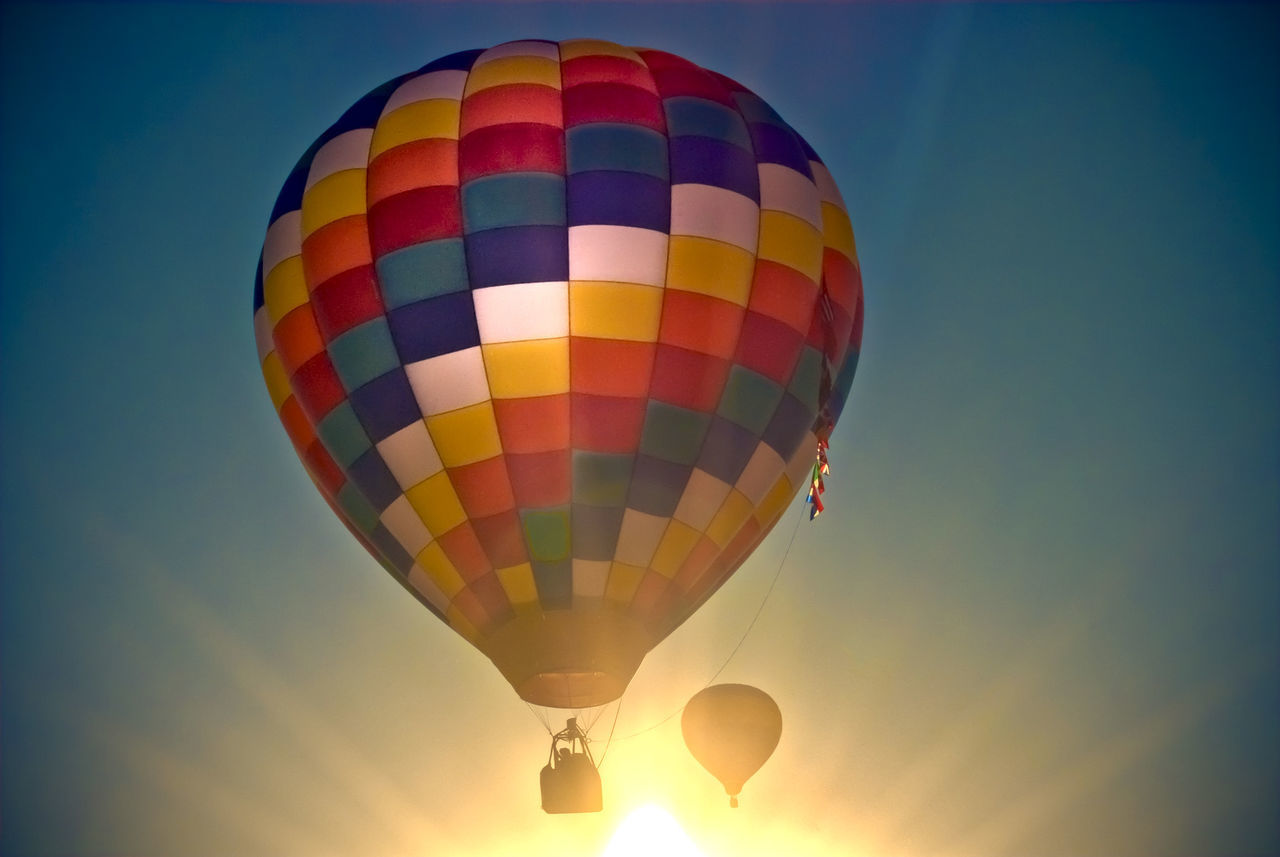 hot air balloon, adventure, low angle view, sky, multi colored, transportation, basket, mid-air, ballooning festival, traditional festival, outdoors, sunset, clear sky, blue, flying, nature, air vehicle, extreme sports, day, no people, beauty in nature