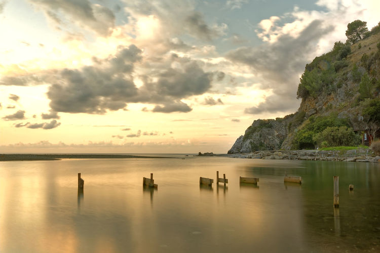 Palinuro. Mingardo river mouth at dawn with cloudy sky and in the background the mingardo rock and the promontory towards marina di camerota Beach Beauty In Nature Cloud - Sky Day Nature No People Outdoors Scenics Sea Sky Sunset Tranquil Scene Tranquility Water