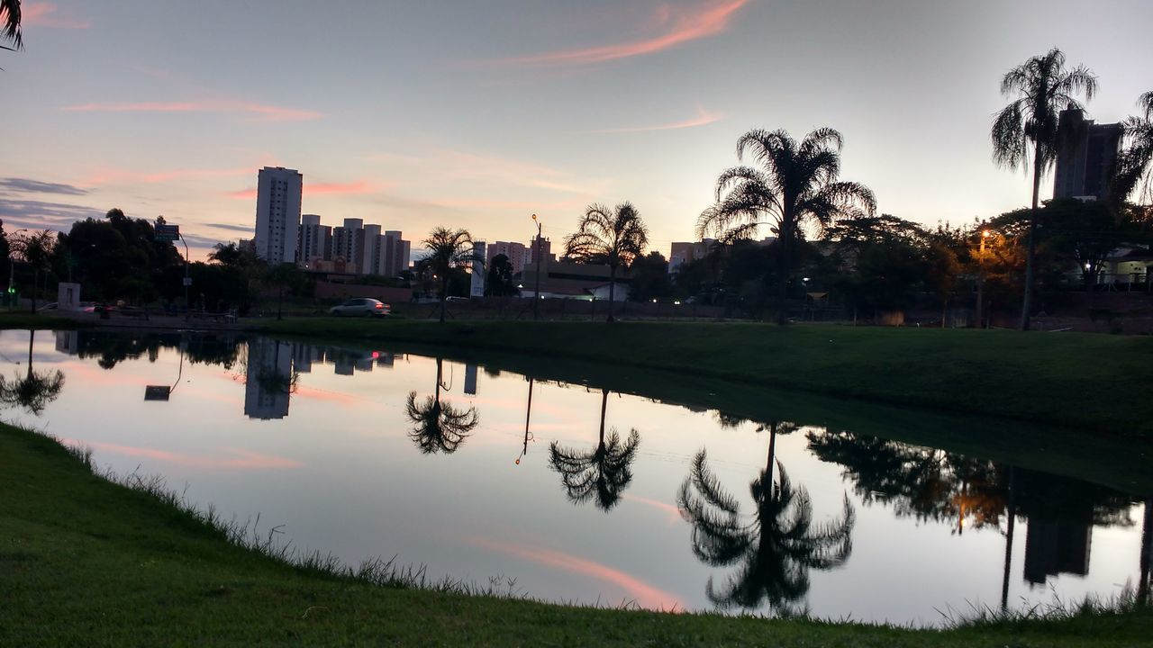 reflection, architecture, building exterior, built structure, water, tree, sky, sunset, waterfront, city, outdoors, skyscraper, no people, growth, cloud - sky, palm tree, travel destinations, lake, modern, grass, nature, cityscape, urban skyline, day