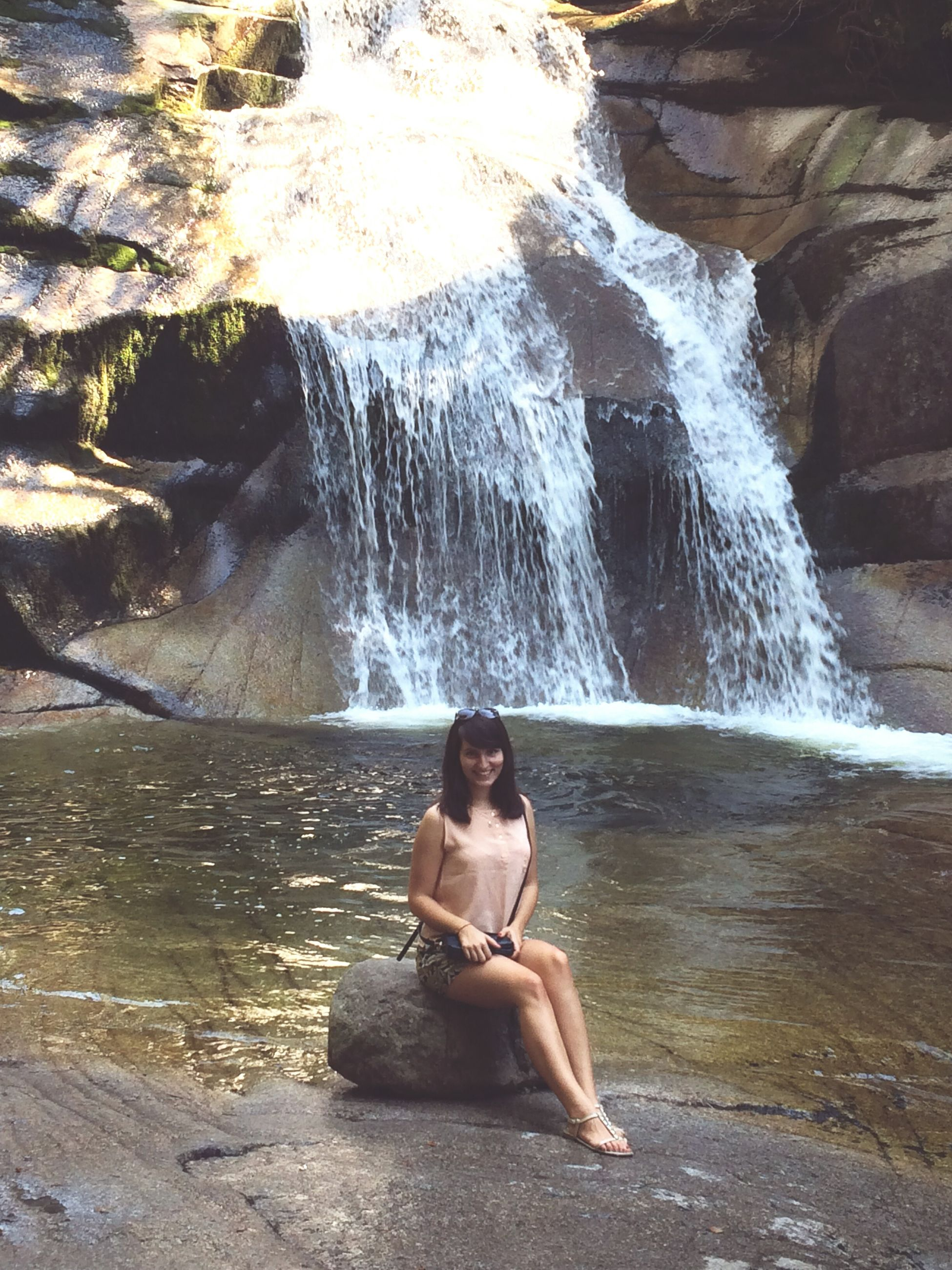 water, rock - object, lifestyles, leisure activity, motion, sitting, full length, rear view, splashing, waterfall, surf, nature, vacations, rock formation, flowing water, beauty in nature, relaxation, day