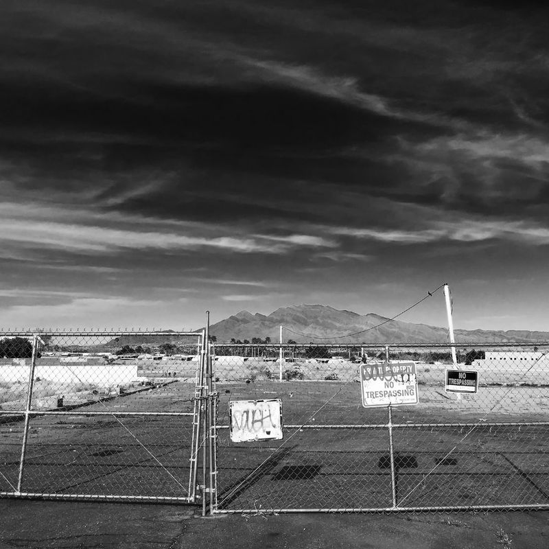 No trespassing signs on fence in desert landscape in the United States - Nevada Black And White Landscape Dark Sky Dramatic Sky EyeEmNewHere Landscape Photography Metal Fence Nevada Desert No Trespassing Square USA Black And White Black And White Photography Day Desert Landscape Iconic Iconic Landscape Landscape Low Vegetation Mountain Nature Nevada No People No Trespassing Sign Square Format
