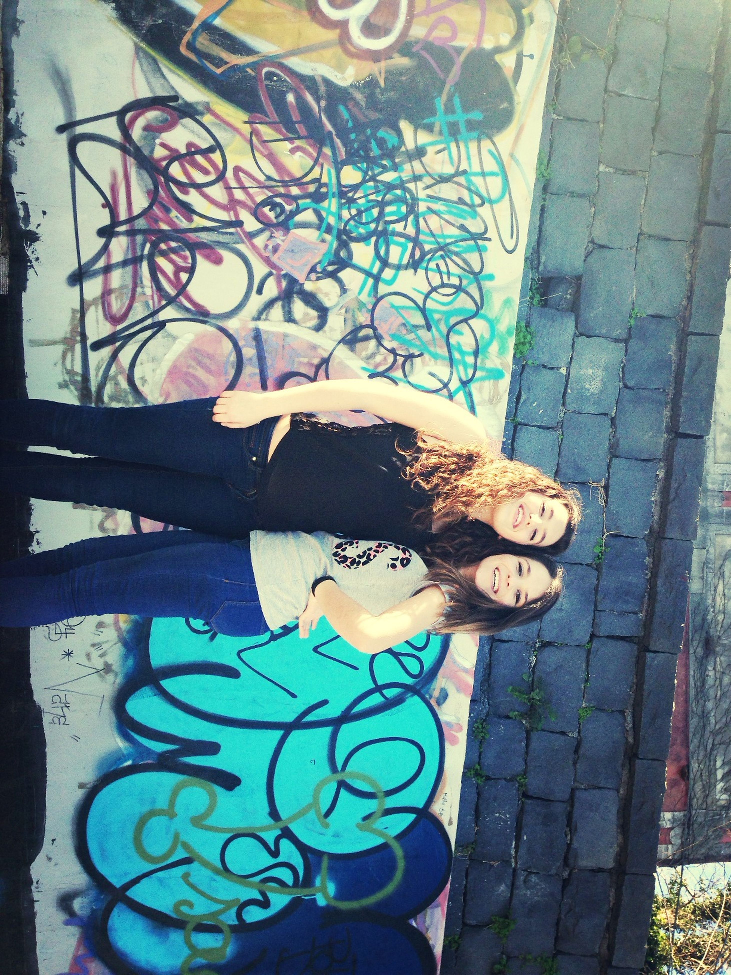 young adult, young women, lifestyles, person, portrait, looking at camera, casual clothing, leisure activity, wall - building feature, standing, three quarter length, graffiti, front view, smiling, long hair, happiness, full length
