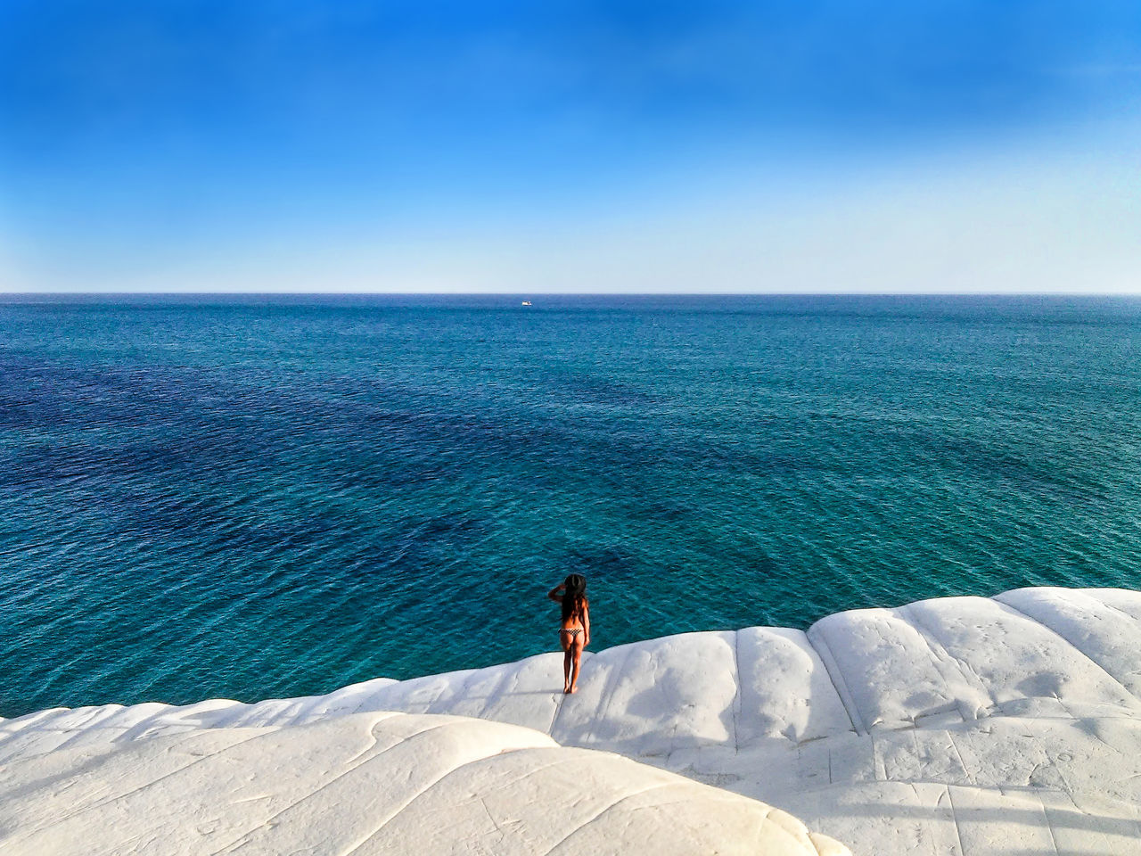 Alone girl standing on the white rock faced to sea Adult Adults Only Beach Beautiful Girl Beauty In Nature Beauty In Nature Blue Day Full Length Girl Girls Horizon Over Water Nature One Person One Woman Only Only Women Outdoors People Sand Scenics Sea Sea And Sky Seascape Sky Waves