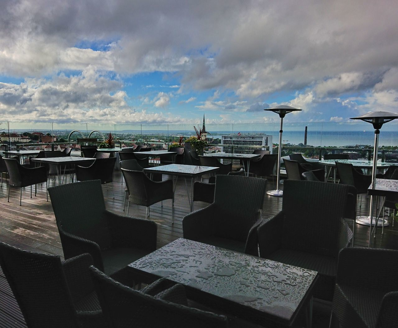 chair, table, sky, outdoor cafe, cloud - sky, empty, restaurant, arrangement, sea, outdoors, place setting, no people, day, nature