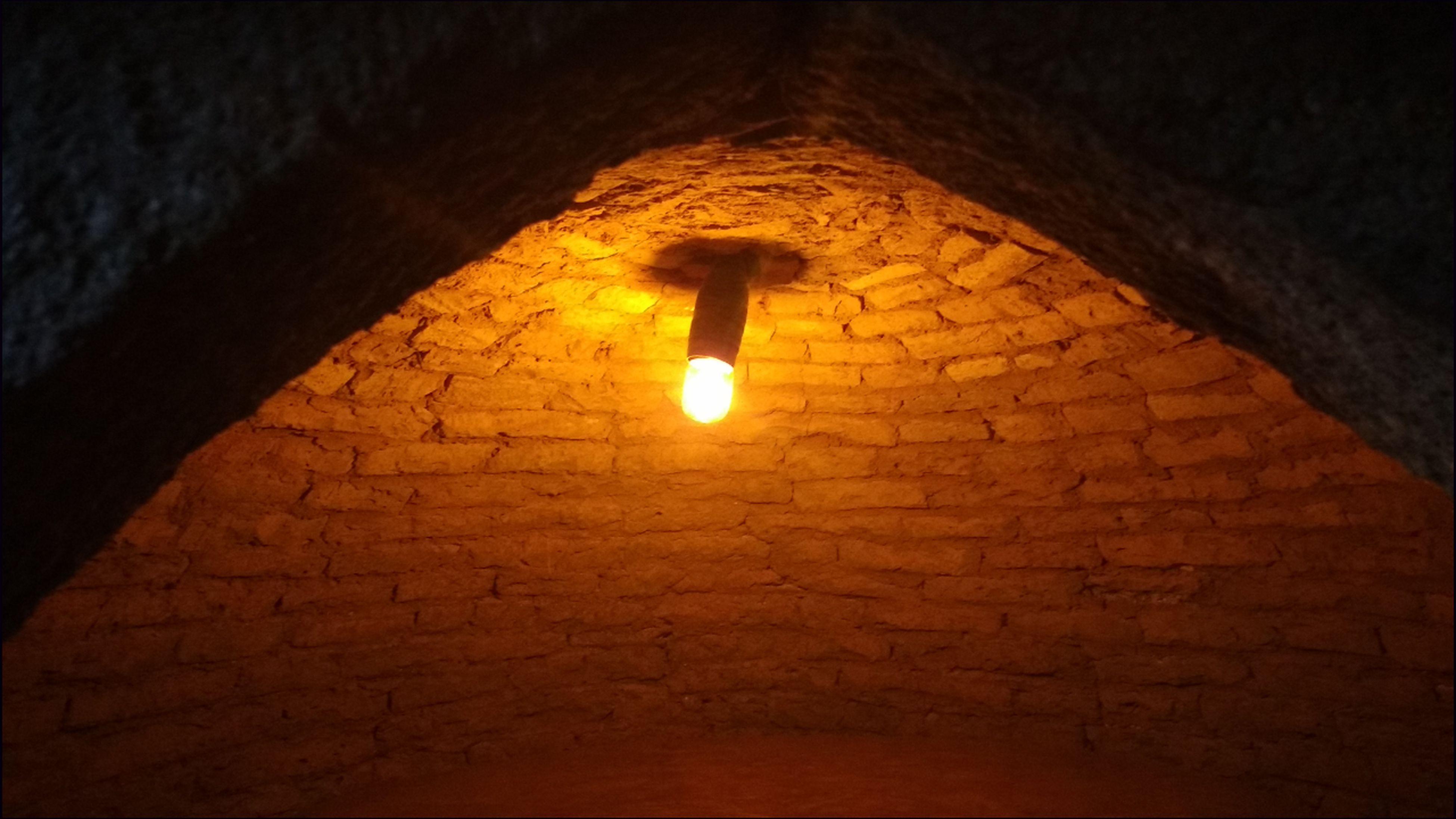 illuminated, lighting equipment, brick wall, night, low angle view, indoors, electricity, no people, architecture, built structure, light bulb